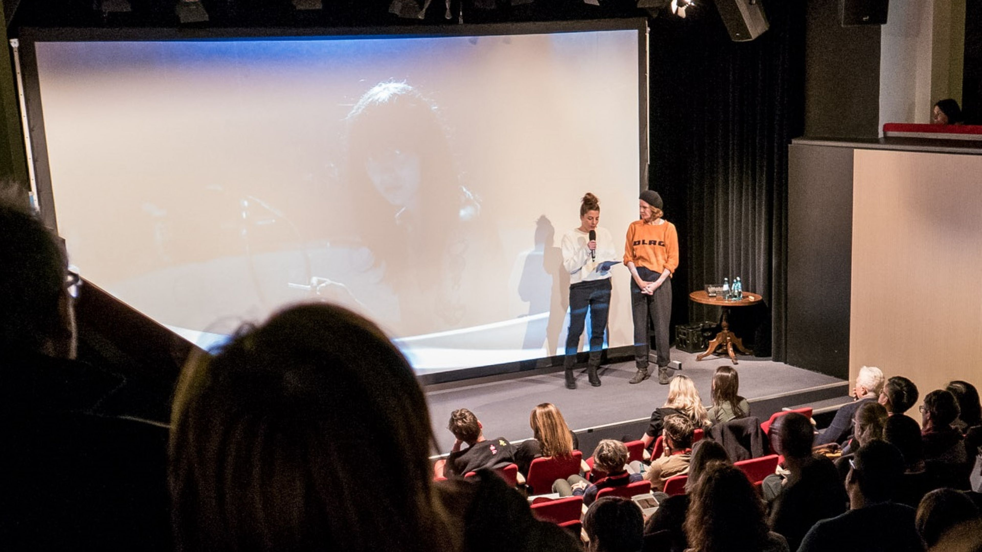 Two woman standing on a stage in front of a big screen talking to the audience