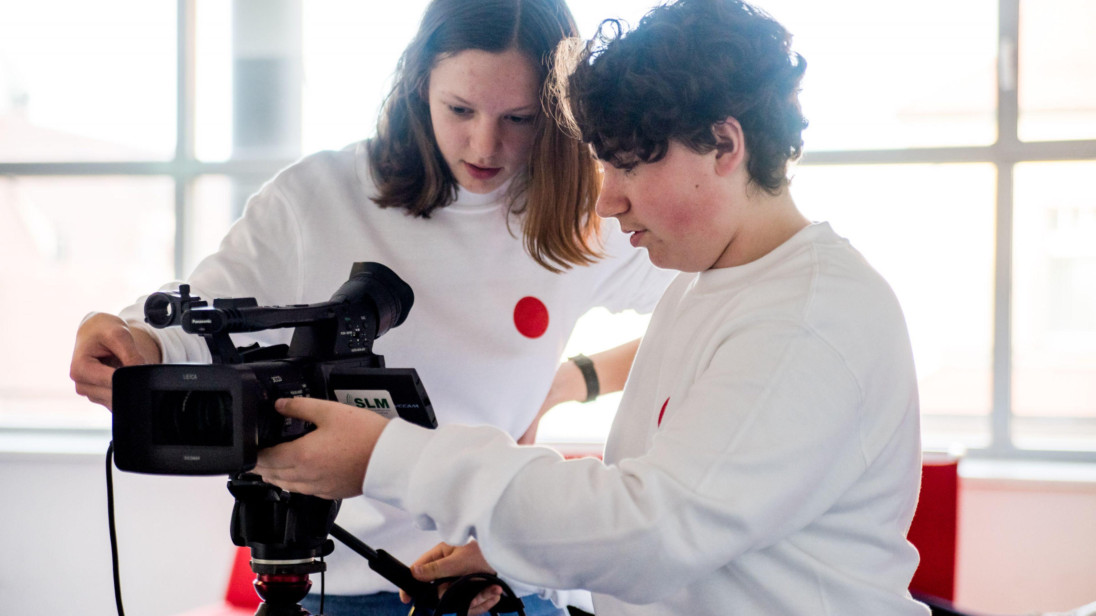 Zwei Jugendliche in weißen DOK Pullovern hantieren mit einer professionellen Kamera.
