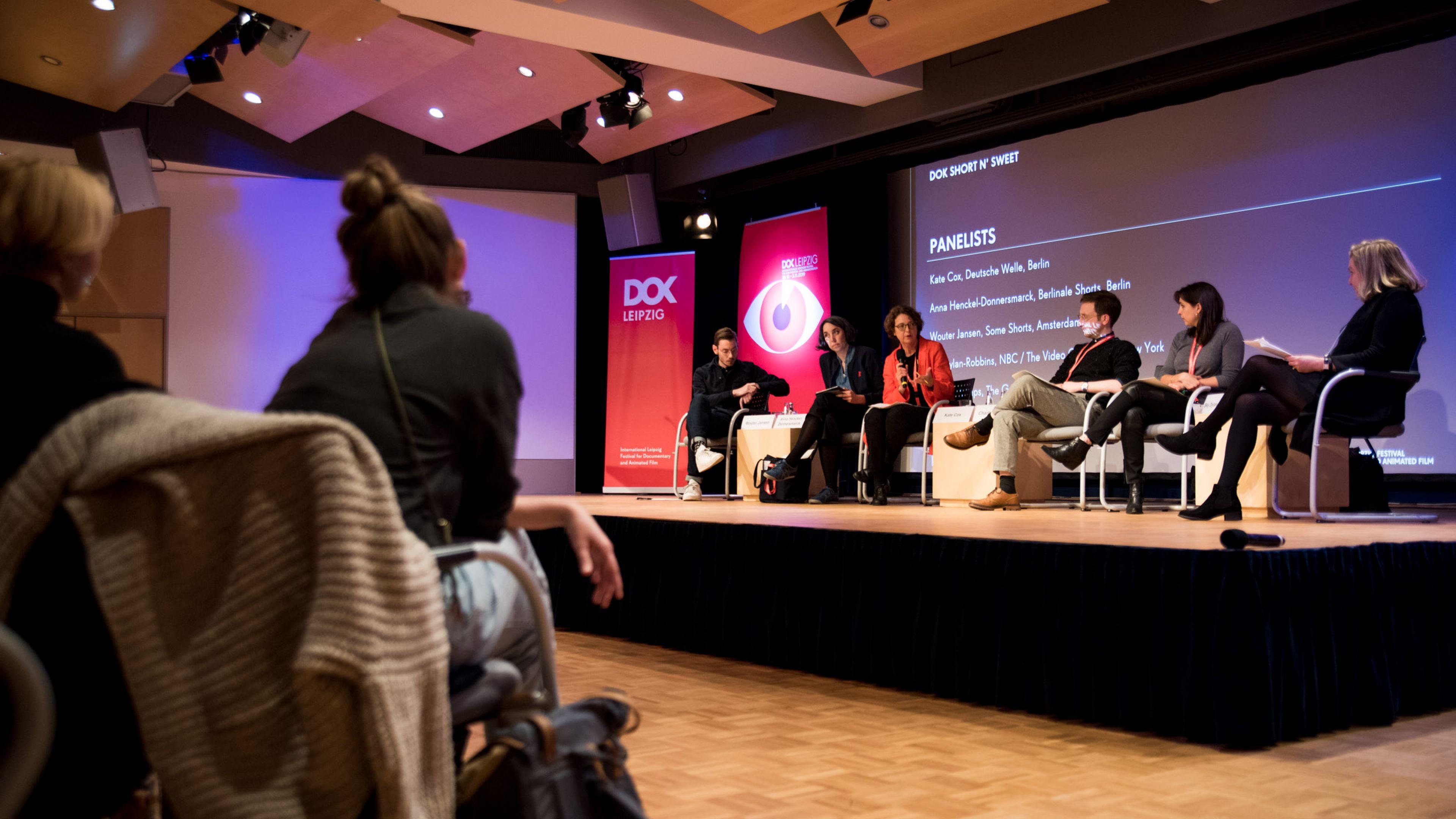 5 Panelteilnehmer sitzen auf einer Bühne vor dem Publikum