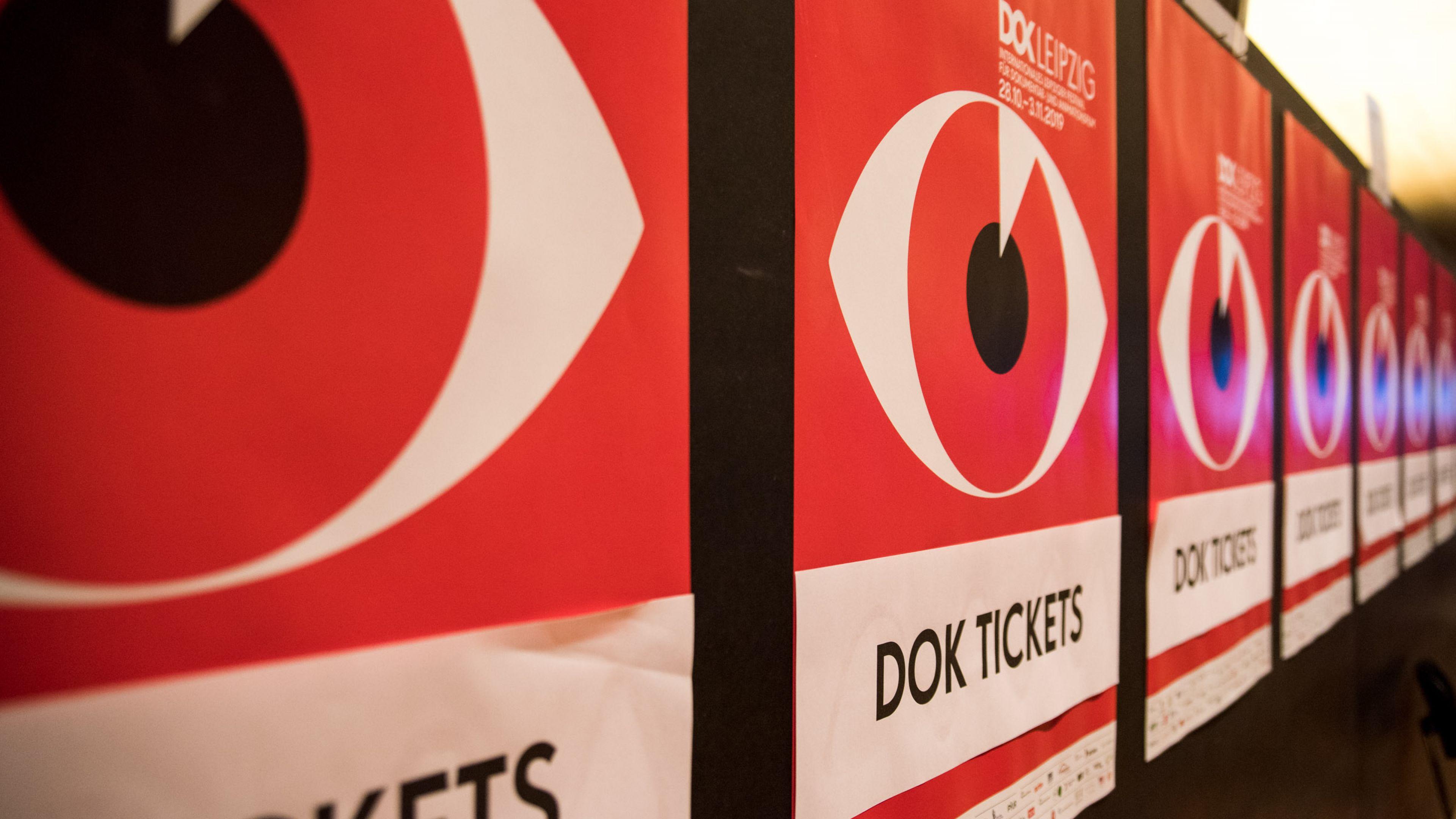 Eine Reihe von roten DOK Leipzig Plakaten mit der Aufschrift Tickets und dem roten Auge als  Festivalmotiv von 2019.