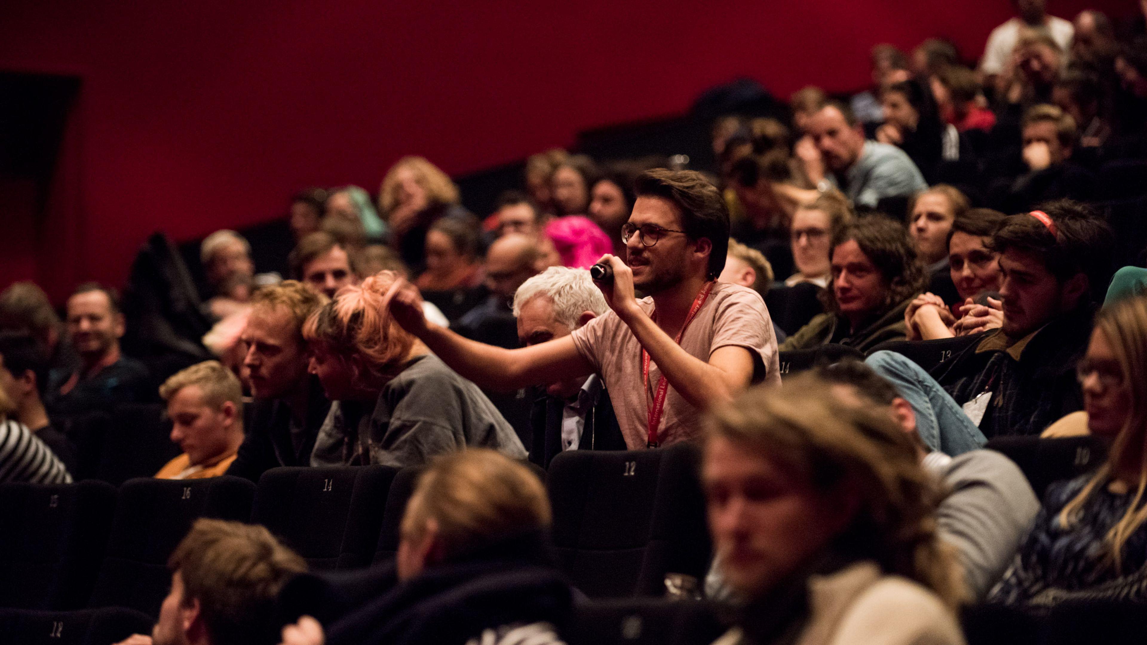 Blick ins gut gefüllte Kinopublikum, ein Mann in der Mitte spricht in ein Mikrofon