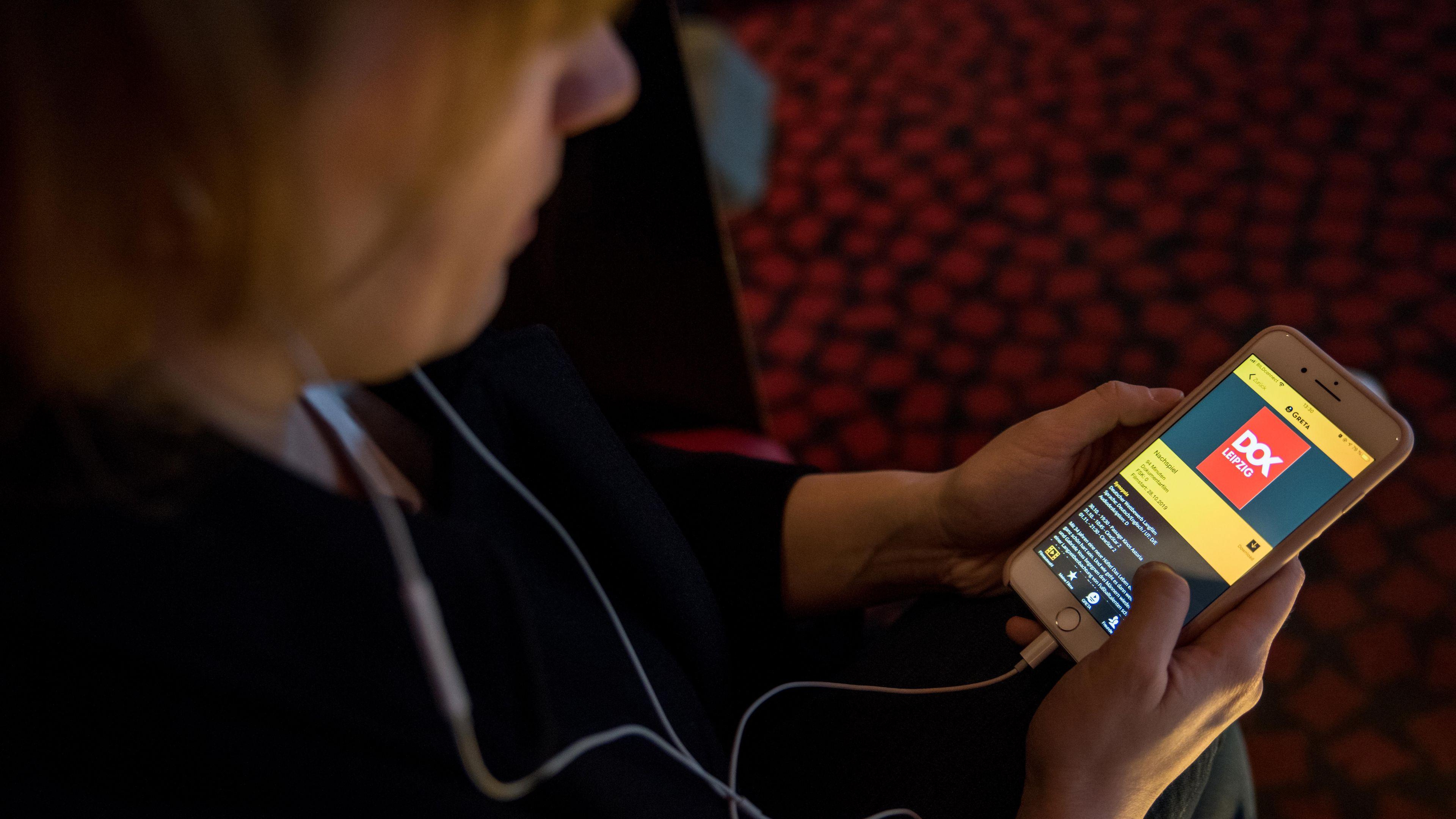 Der*die Betrachter*in sieht über die Schulter einer Frau auf einen Handybildschirm, der eine App für Audiodeskription zeigt