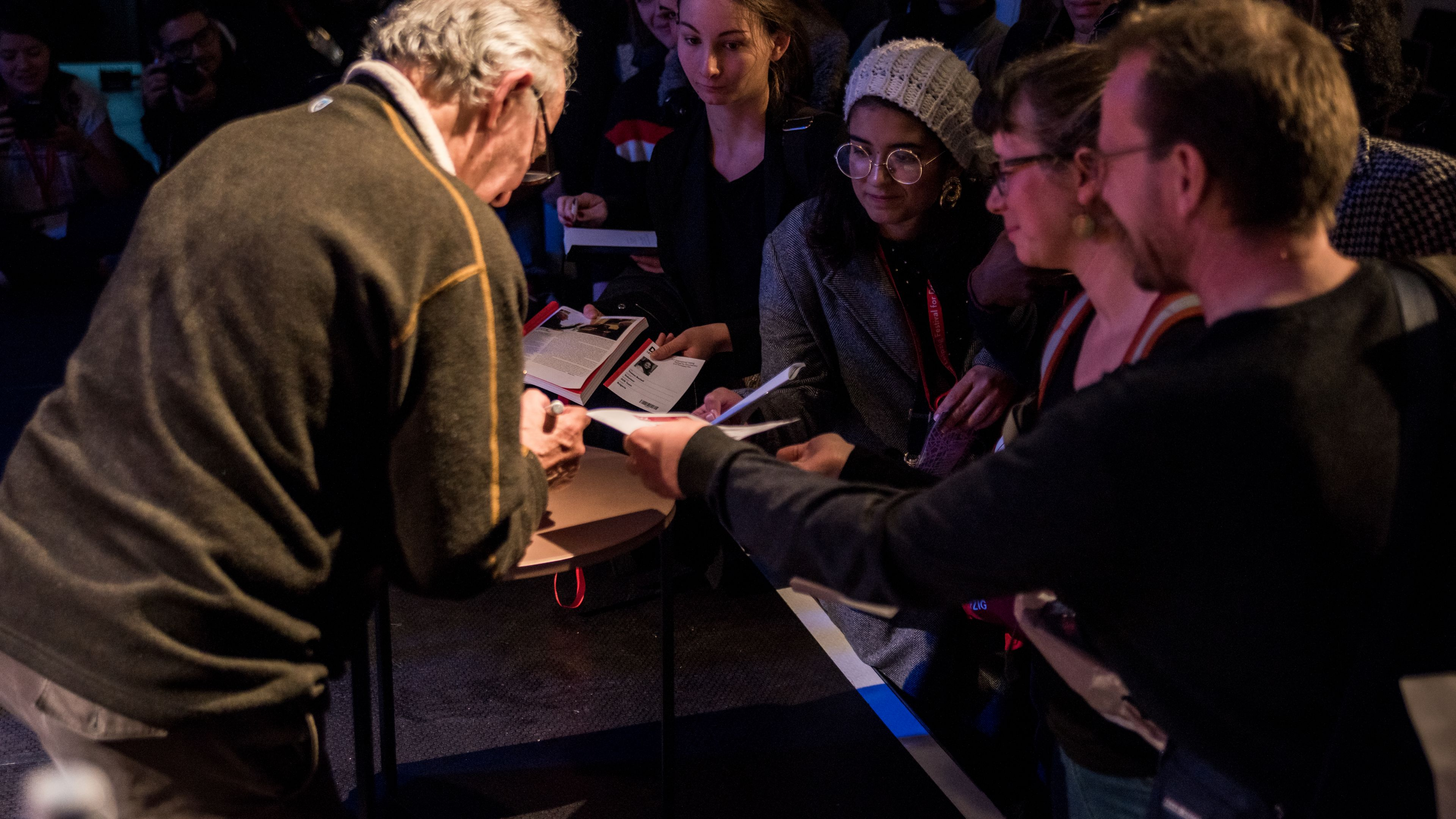 Werner Herzog knees on stage, many people before the stage try to hand him their programms for an autograph