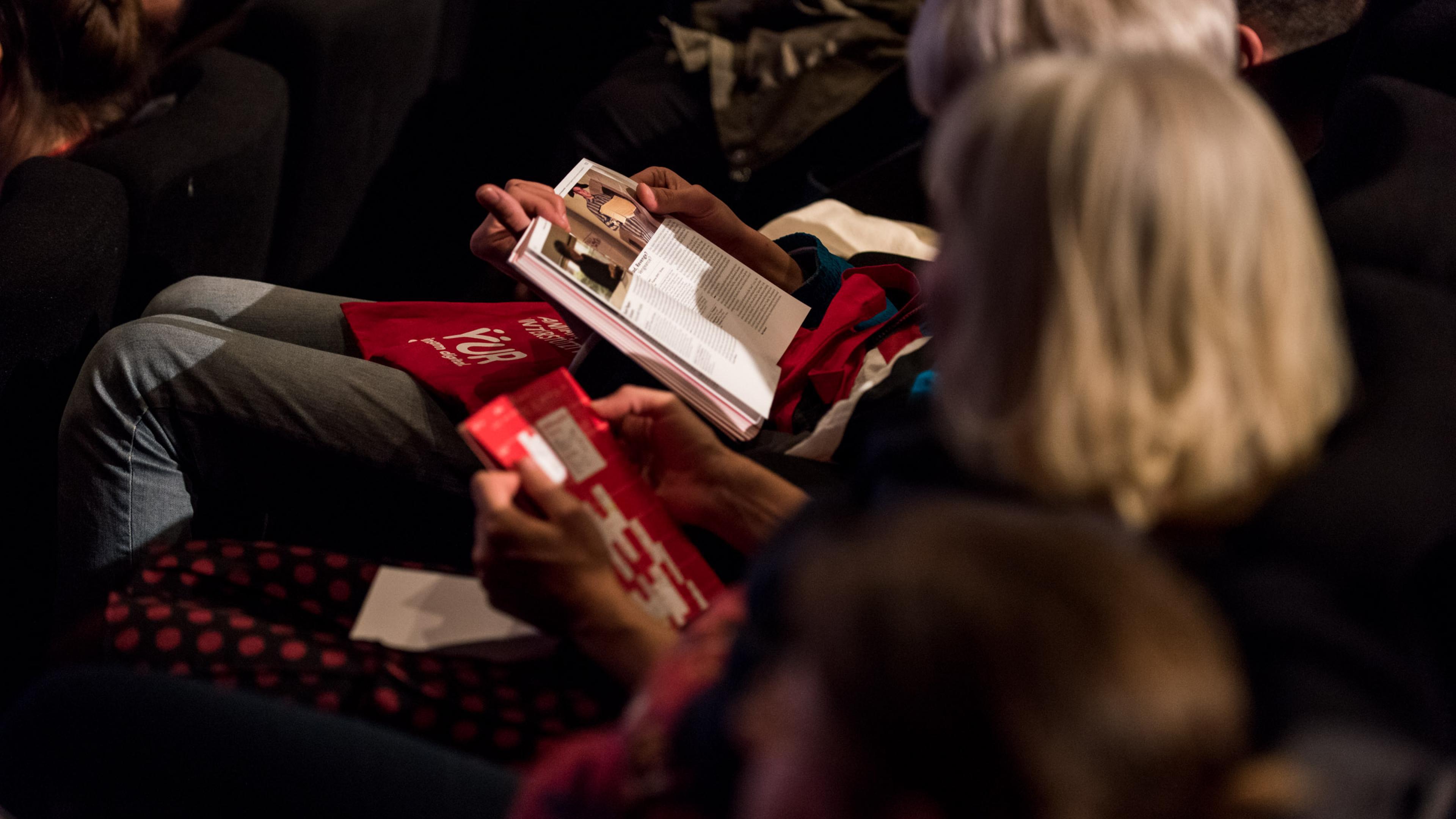 Zuschauerinnen in einer Kinoreihe lesen im DOK Leipzig Programmheft.