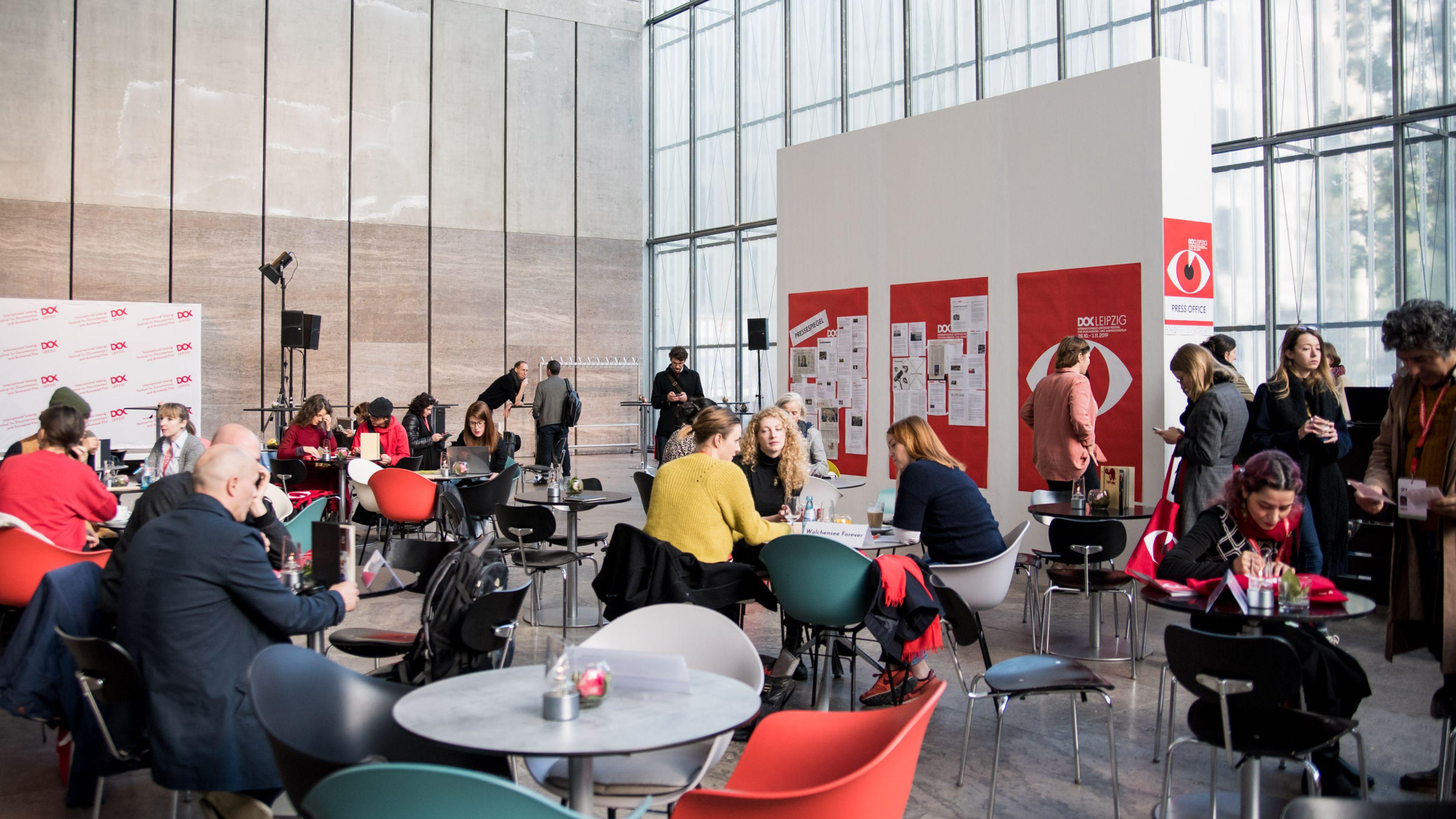 Das Festivalzentrum, viele Menschen sitzen an runden Tischen und trinken Kaffee