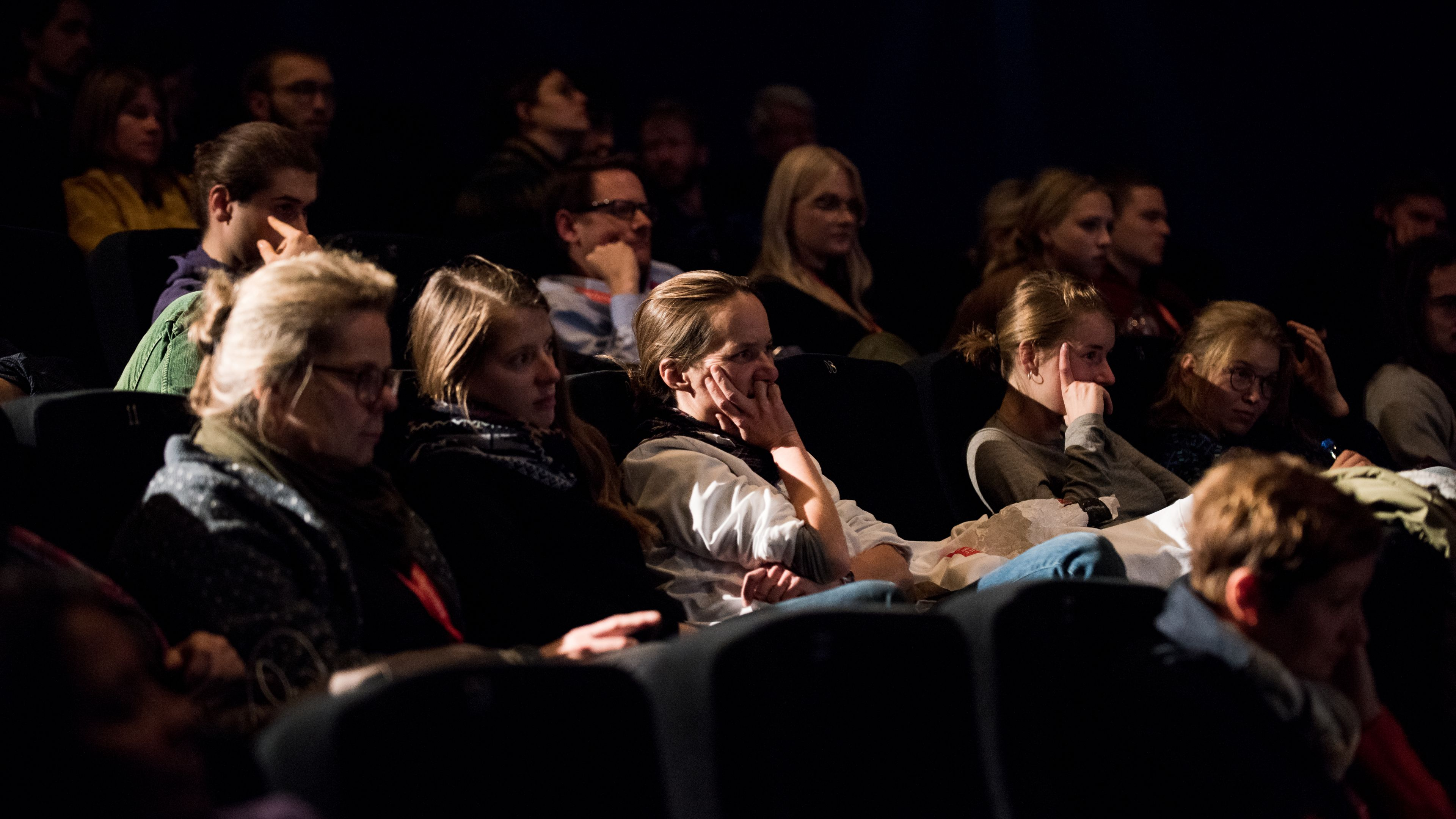 Vier Zuschauerinnen nebeneinander in einer Sitzreihe hören interessiert zu.
