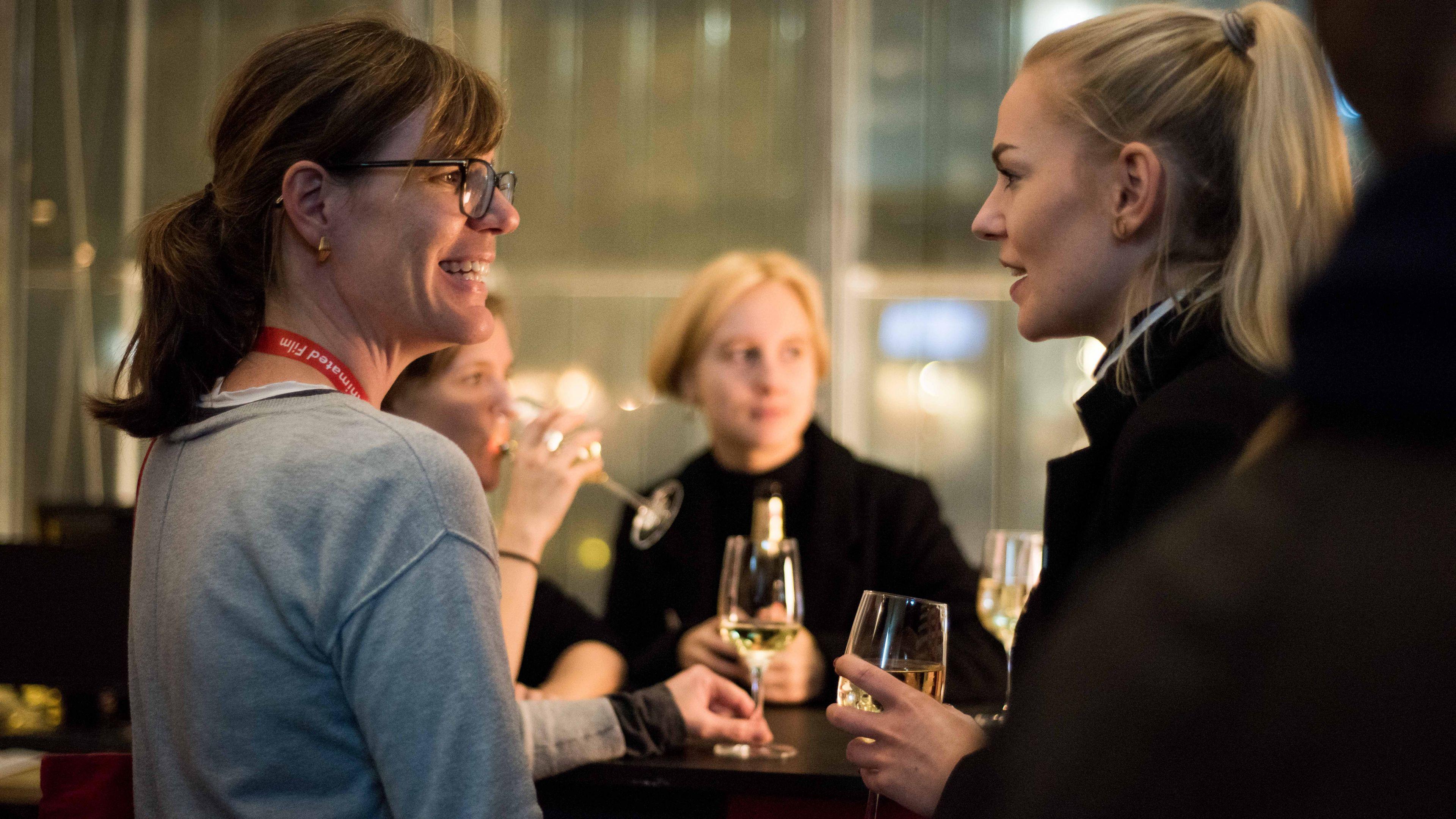 Zwei Frauen mit Sektgläsern in der Hand unterhalten sich bei einer Abendveranstaltung. Die Frau links lächelt.