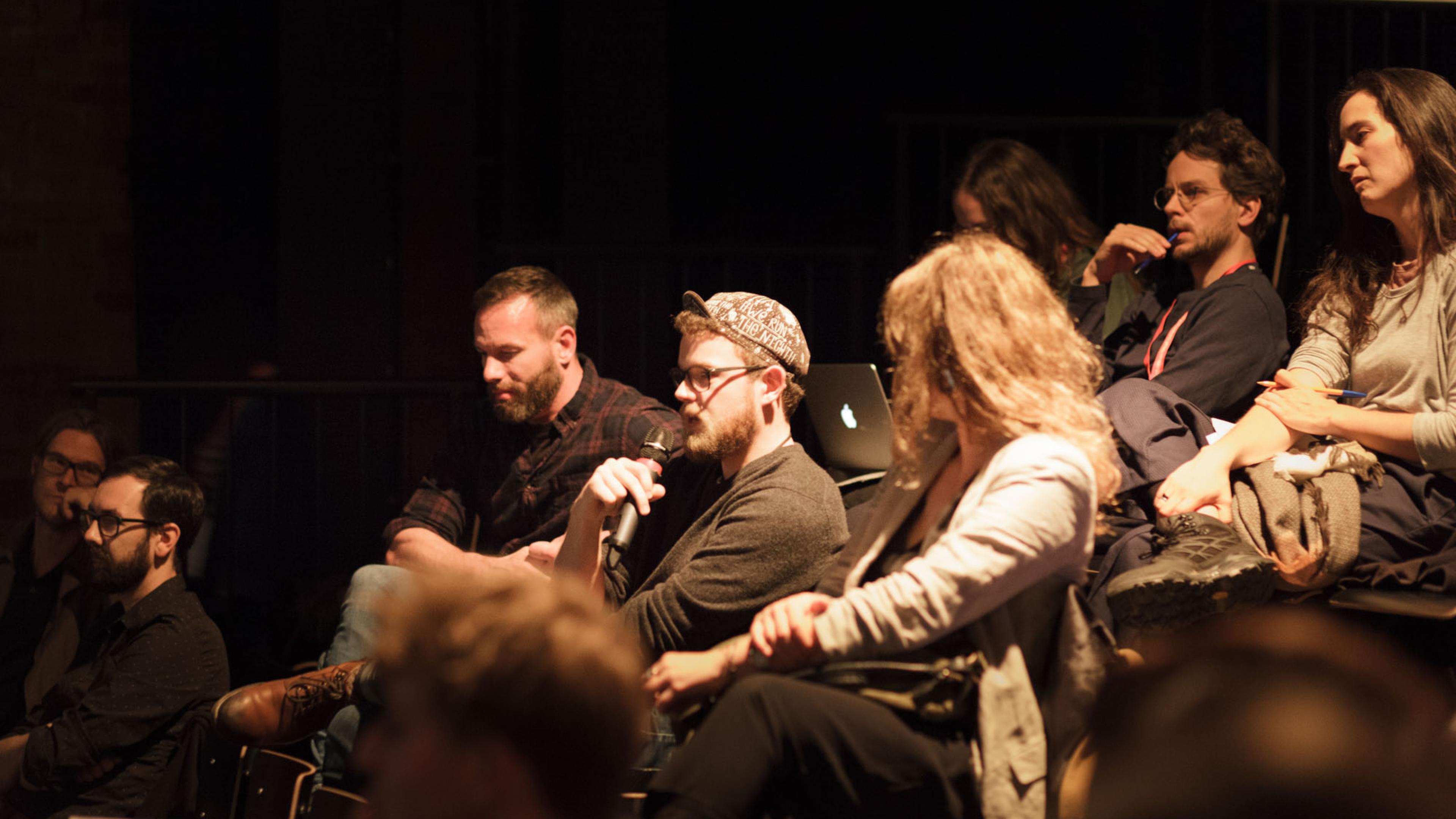 Mann sitzt in einem Vortragsraum im Publikum und spricht in ein Mikrofon, die Personen um  ihn herum schauen ihn an.