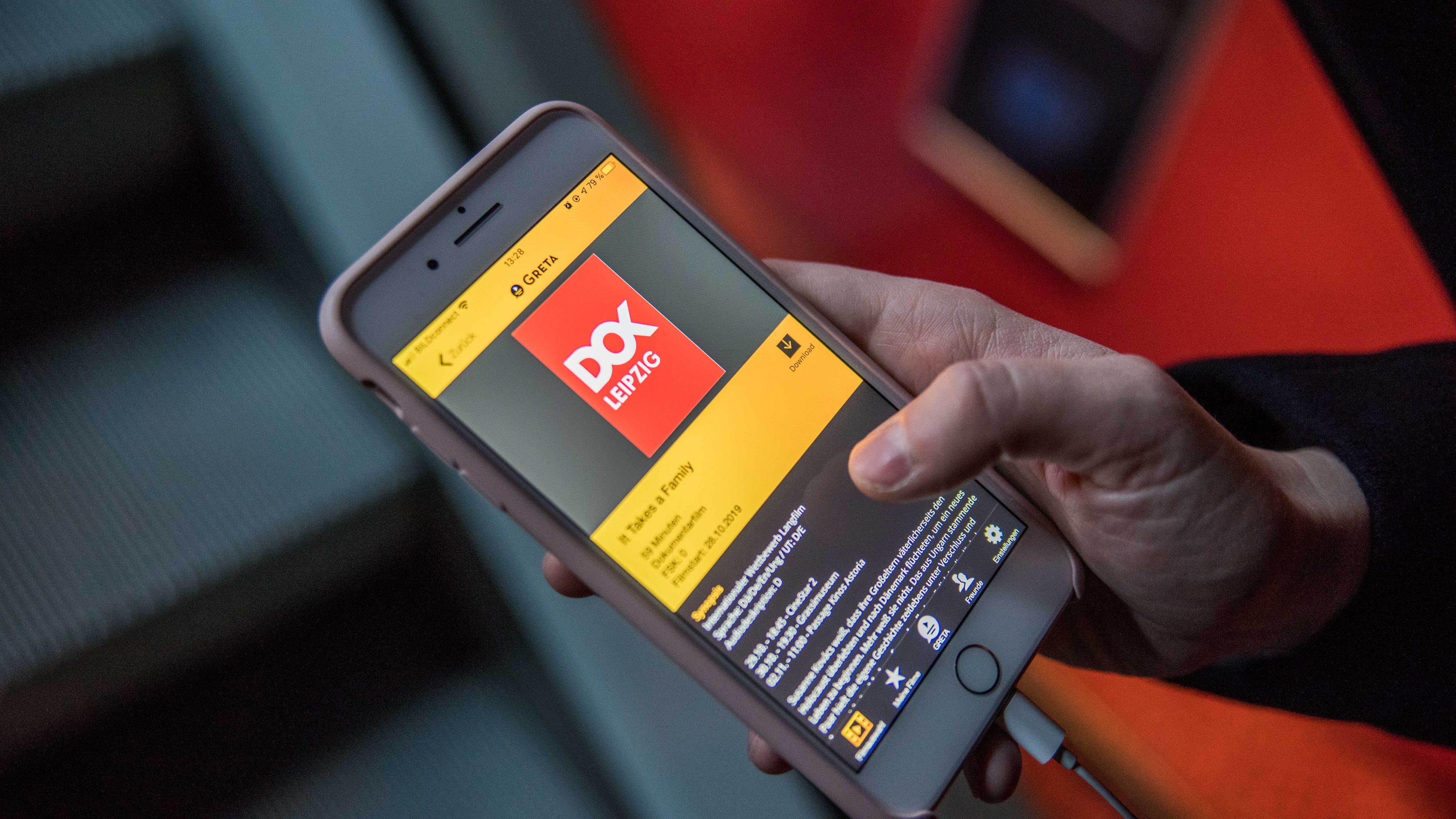 Eine Besucherin, von der nur die rechte Jand zu sehen ist, hält darin ihr Smartphone. Auf dem Display erscheint die App Greta, ausgewählt ist der Film It Takes a Family.