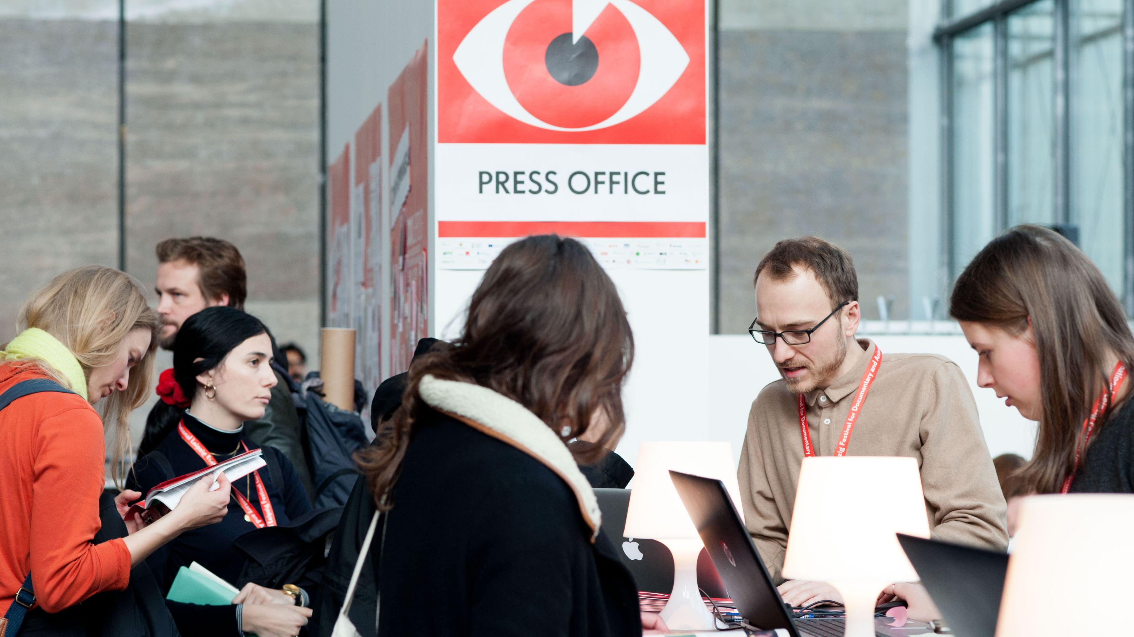 Mehrere Personen im Gespräch am Gästecounter im Festivalzentrum 2019