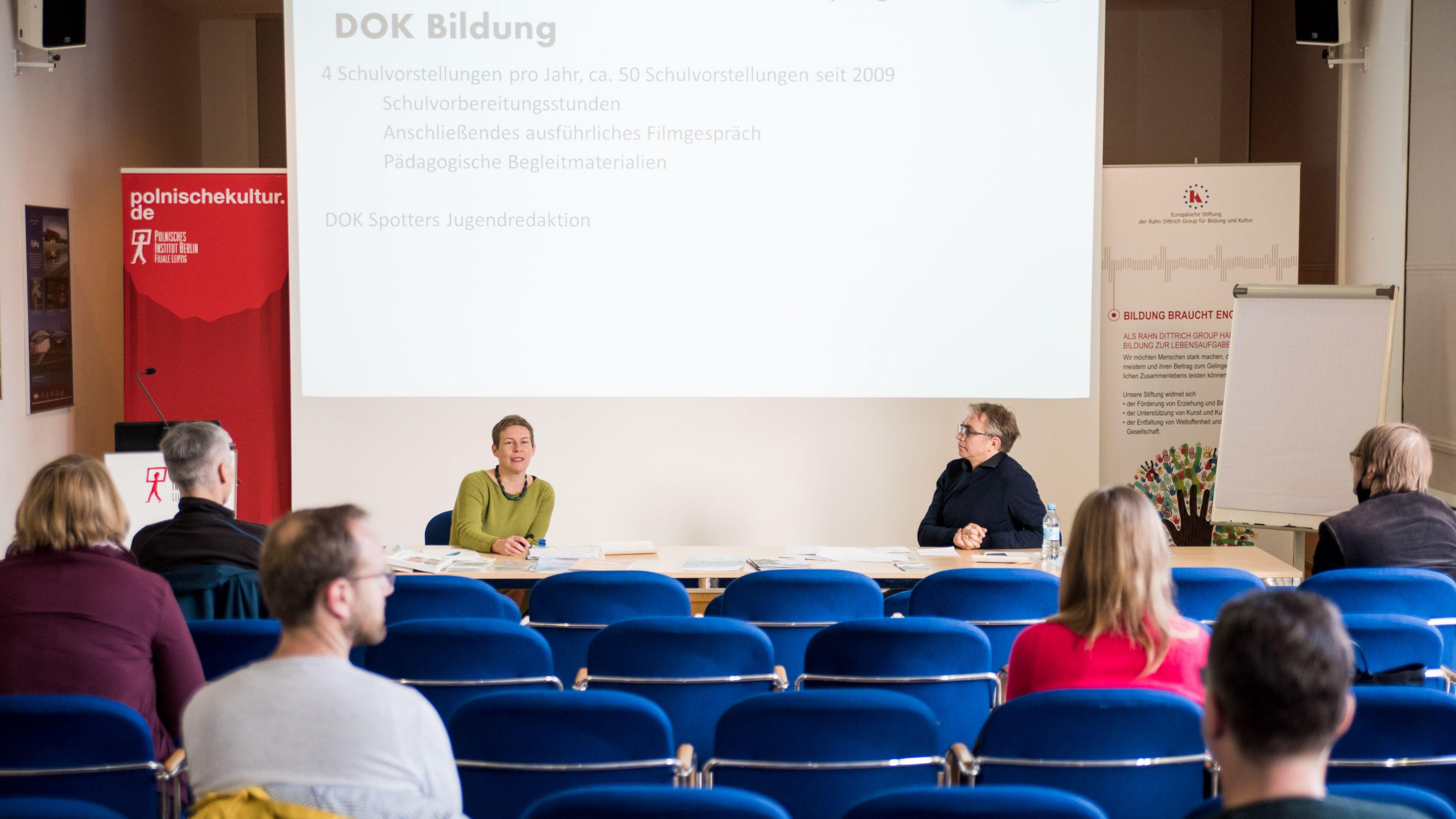 Ein Konferenzraum mit einer Frau und einem Mann, die auf dem Podium sitzen und zum Publikum sprechen, hinter ihnen eine Leinwand.