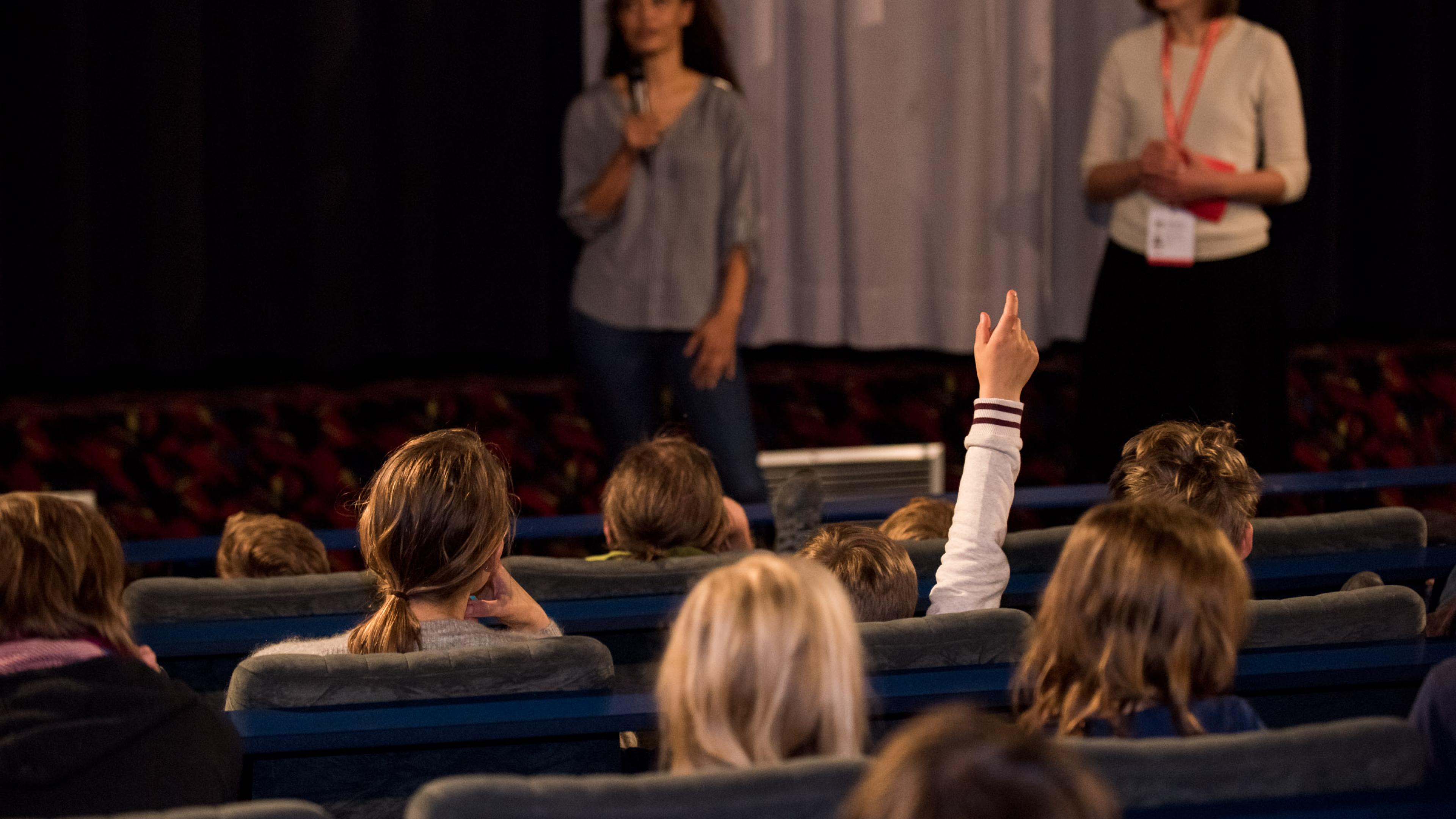 Blick von hinten über die Zuschauerreihen in einem Kinosaal, vorne bei der Leinwand  stehen zwei Frauen mit Mikrofon in der Hand.