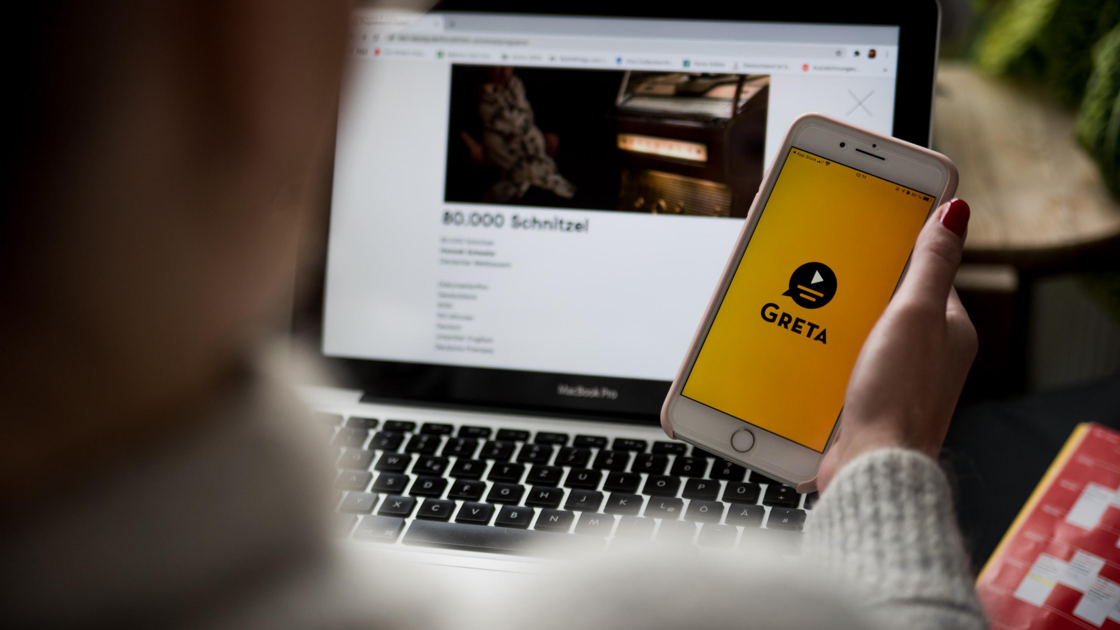 Blick über die Schulter einer Person auf ihren Laptopbildschirm, in der Hand hält sie ein Smartphone mit dem Startbildschirm der App Greta.