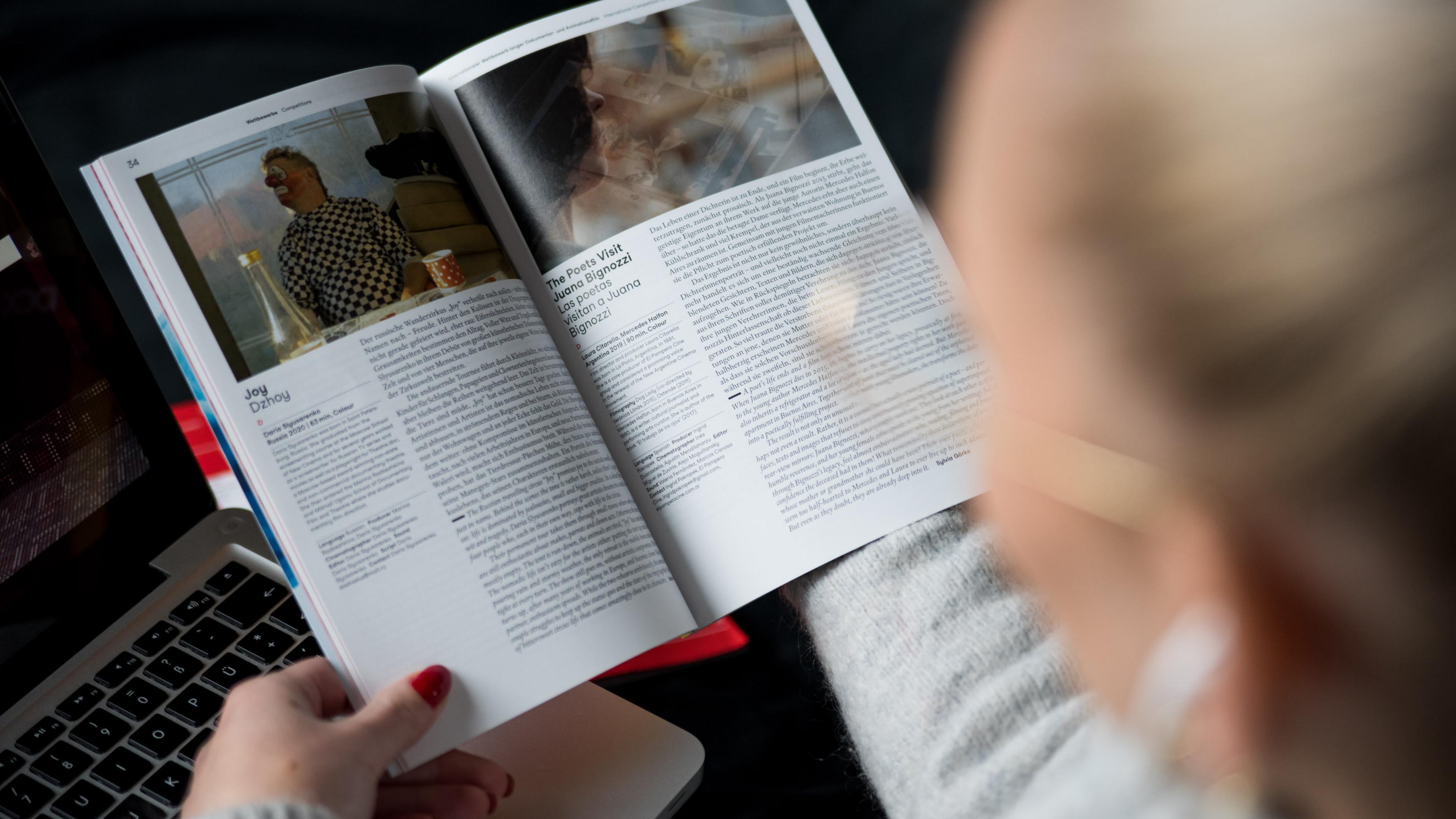Eine Frau blättert im DOK Festivalkatalog von 2021, die Kameraperspektive blickt über ihre Schulter auf den Katalog in ihrer Hand.