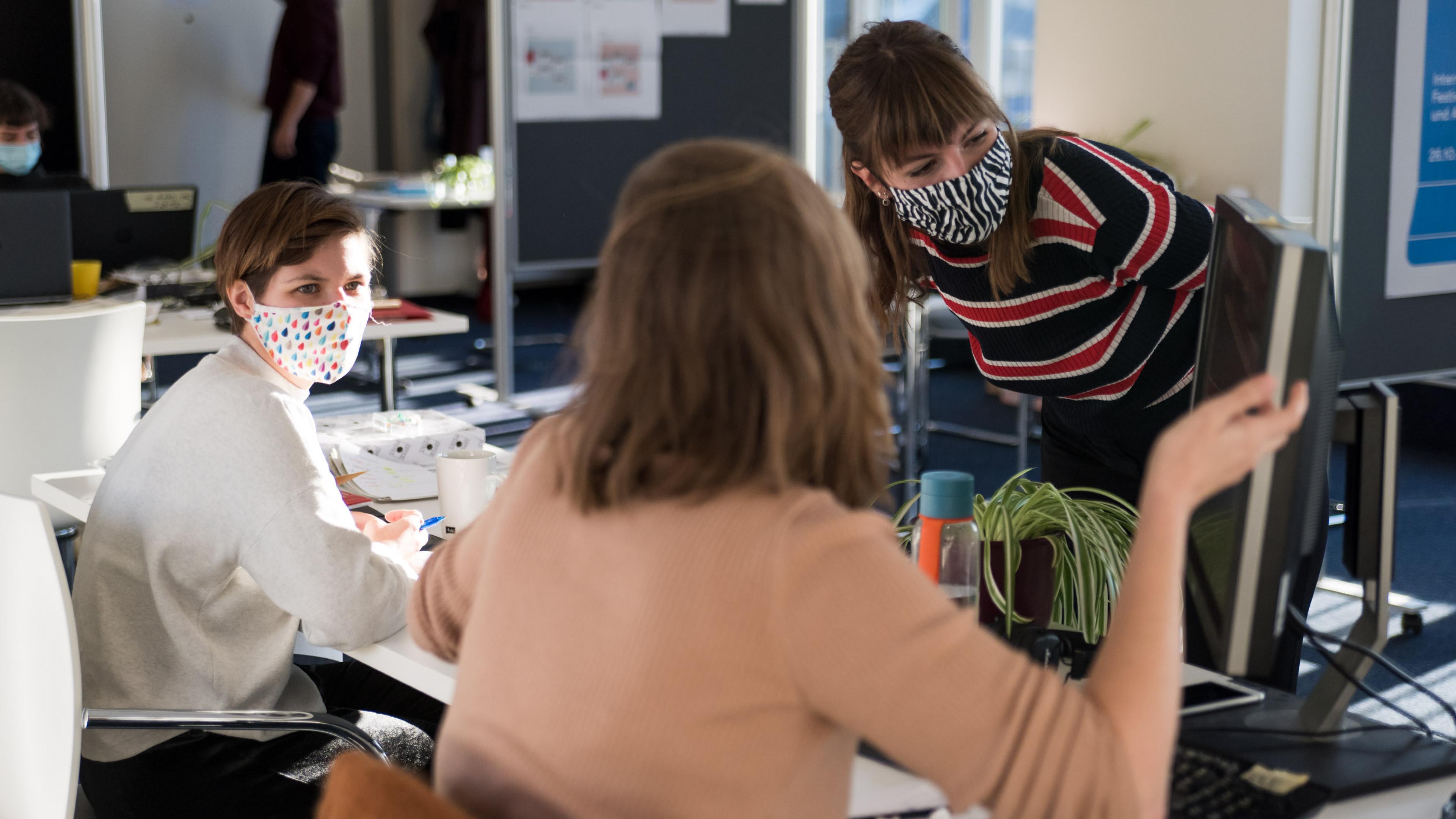 Drei weibliche Personen beugen sich über einen Computerbildschirm und gestikulieren dabei.
