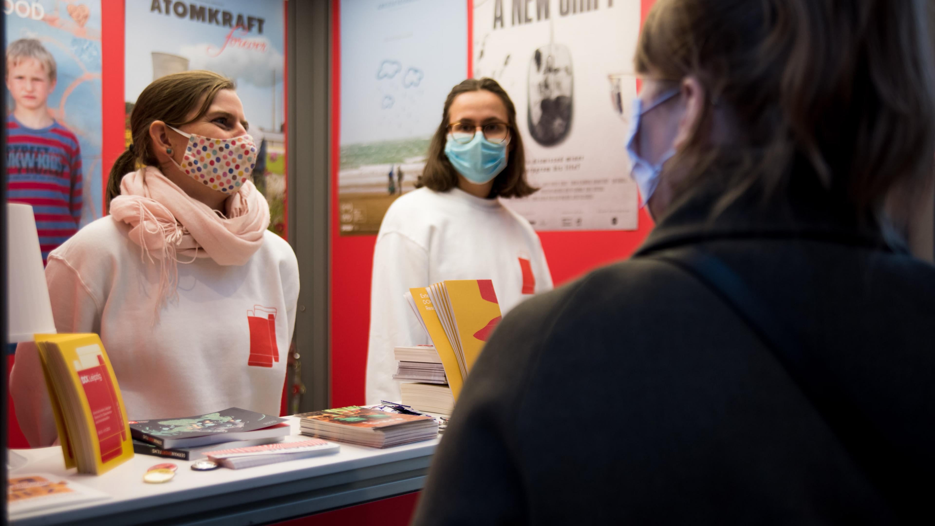 Zwei Volunteers mit DOK Pullis im Gespräch mit einer Besucherin am Info-Schalter.