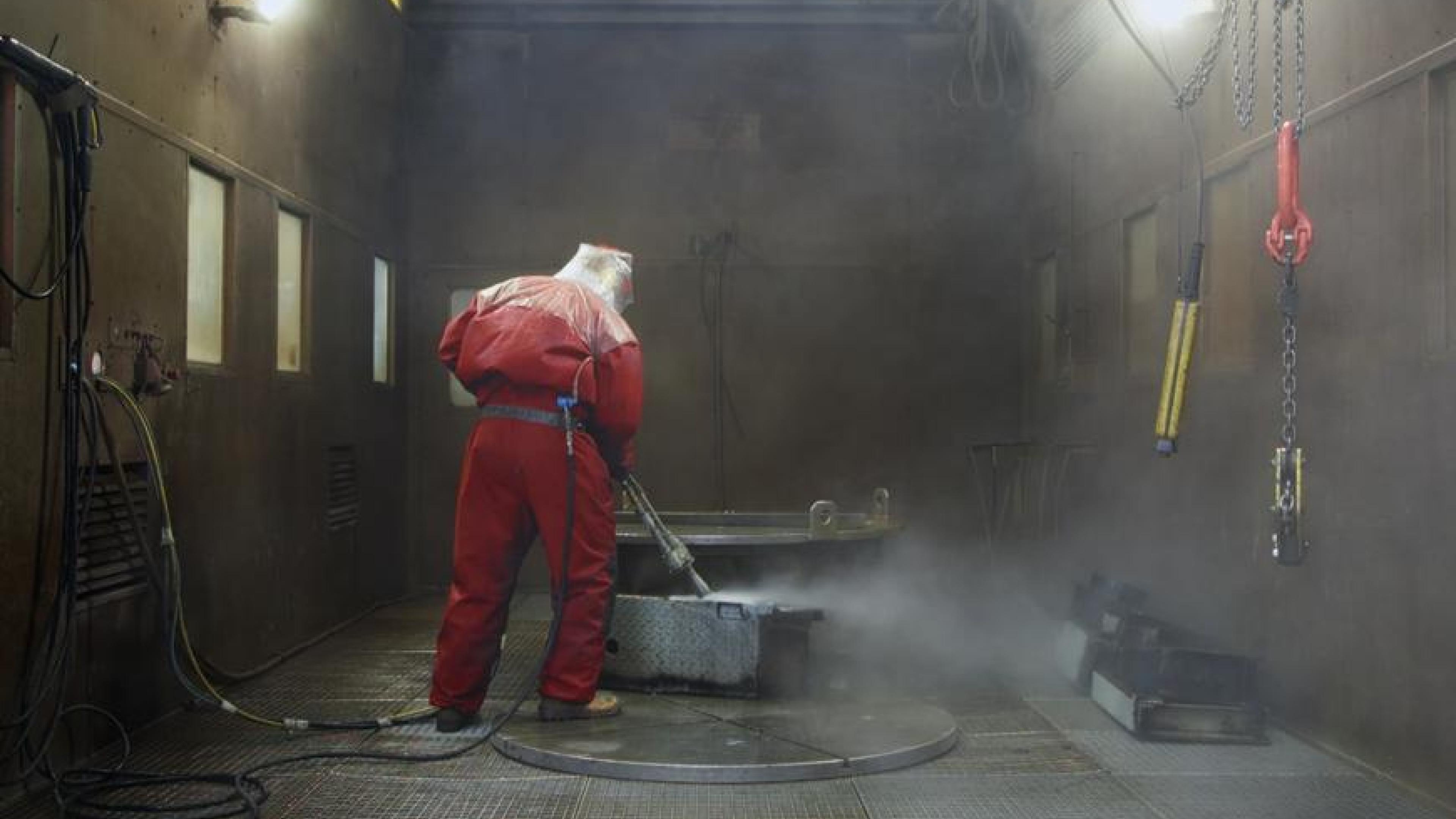 Ein Mann in einem roten Schutzanzug reinigt mit einen Hochdruckreiniger einen Metallkasten.