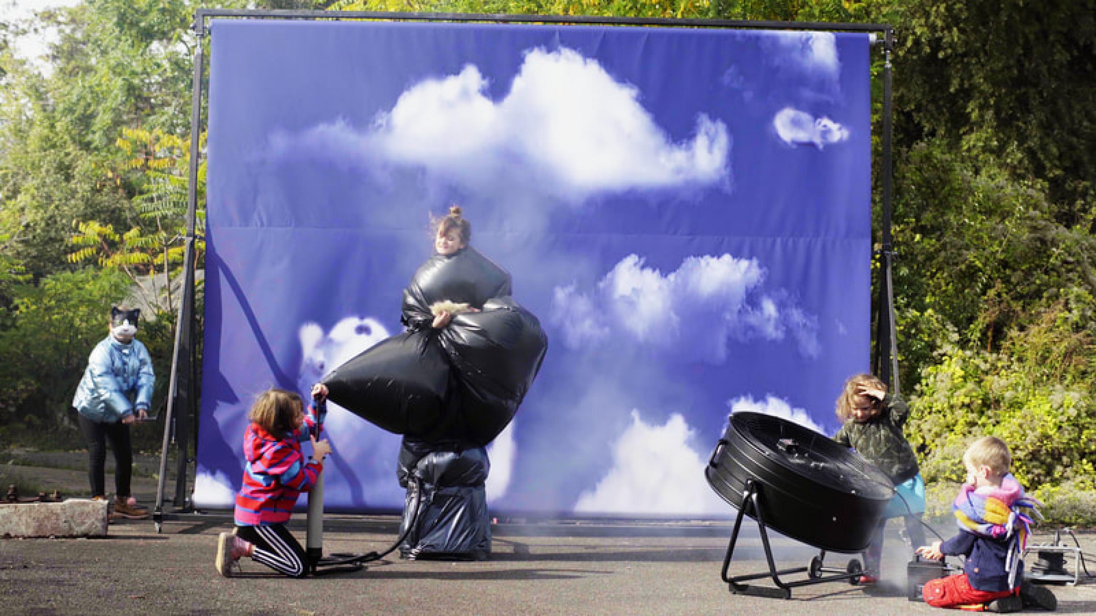 Fünf Kinder drehen in einem Filmset, im Hintergrund eine Leinwand mit Abspann, rechts steht eine Windemaschine.