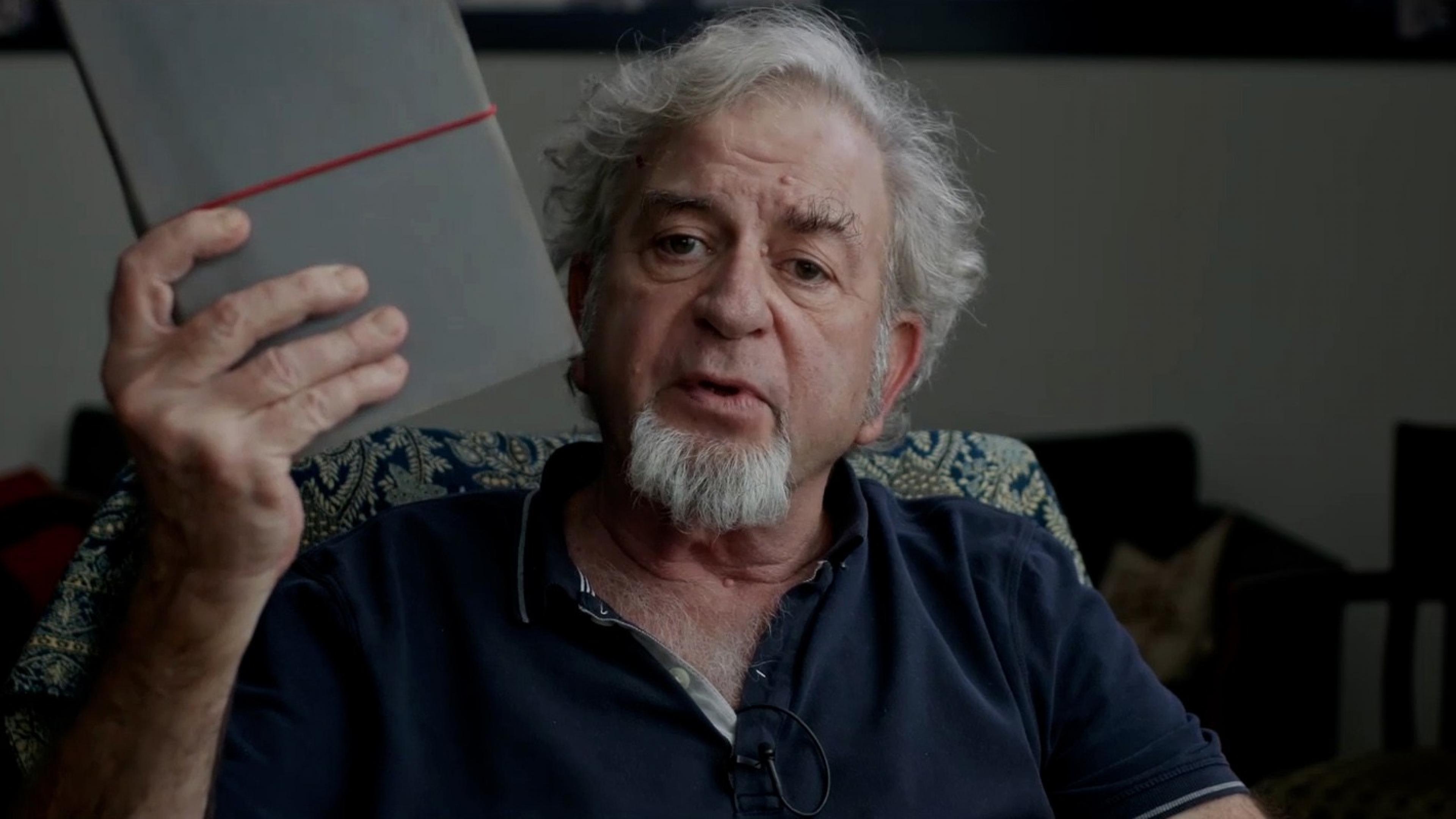 Regisseur Avi Mograbi blickt in die Kamera, spricht dabei und hält dabei in der rechten Hand ein Notizbuch hoch.
