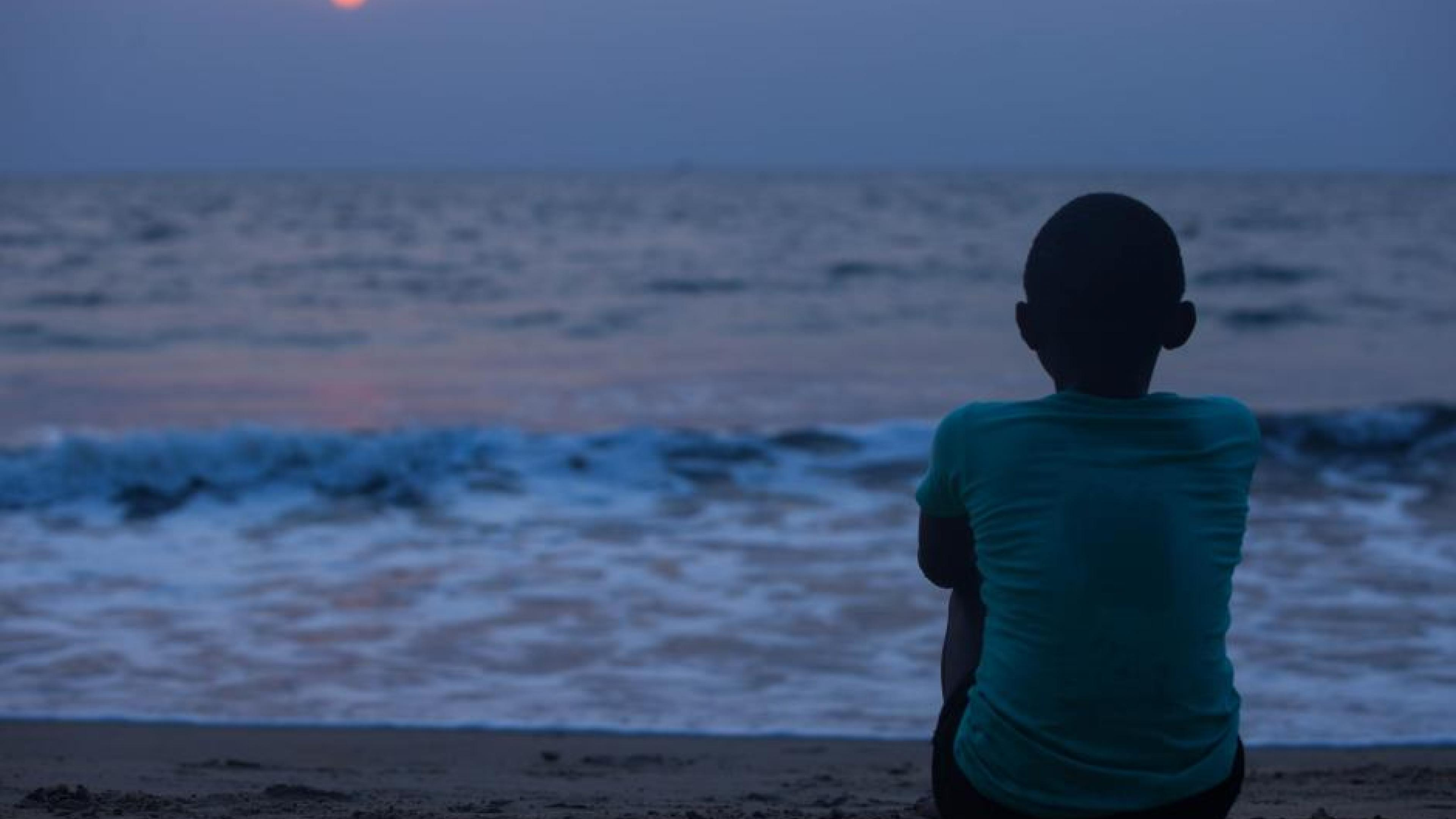 Film Still from Njel. A black boy facing the sea in the sunset.