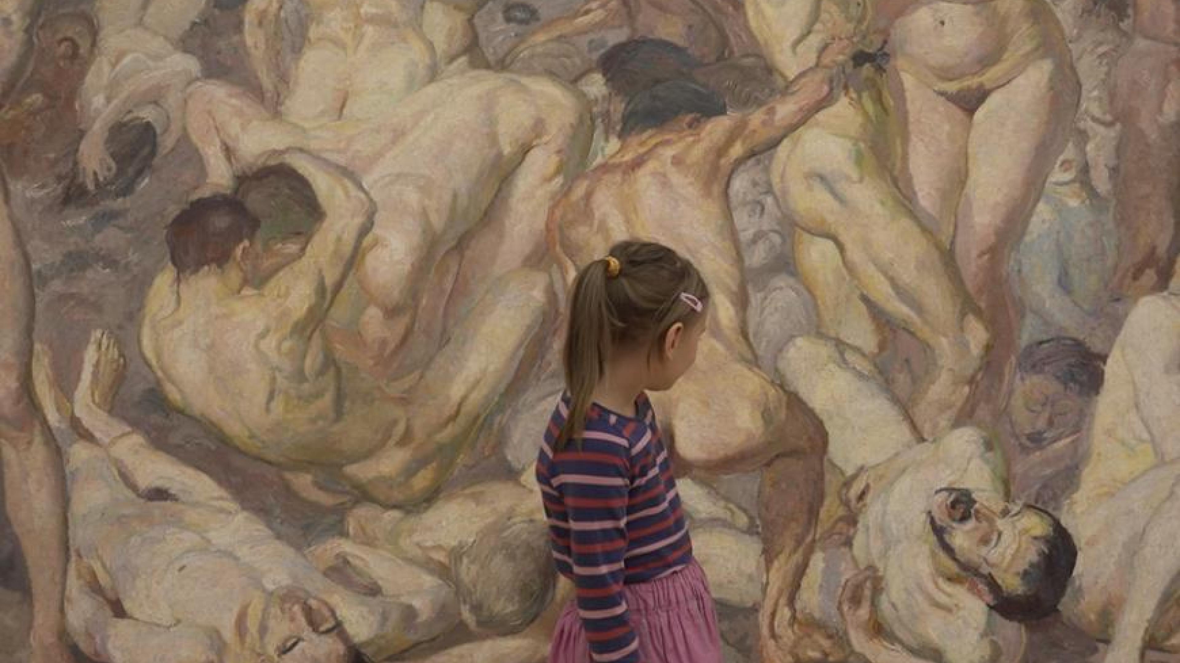 Ein junges Mädchen in geringeltem Pulli und Rock steht vor einem riesigen Gemälde, das viele nackte, verschlungene Menschen zeigt