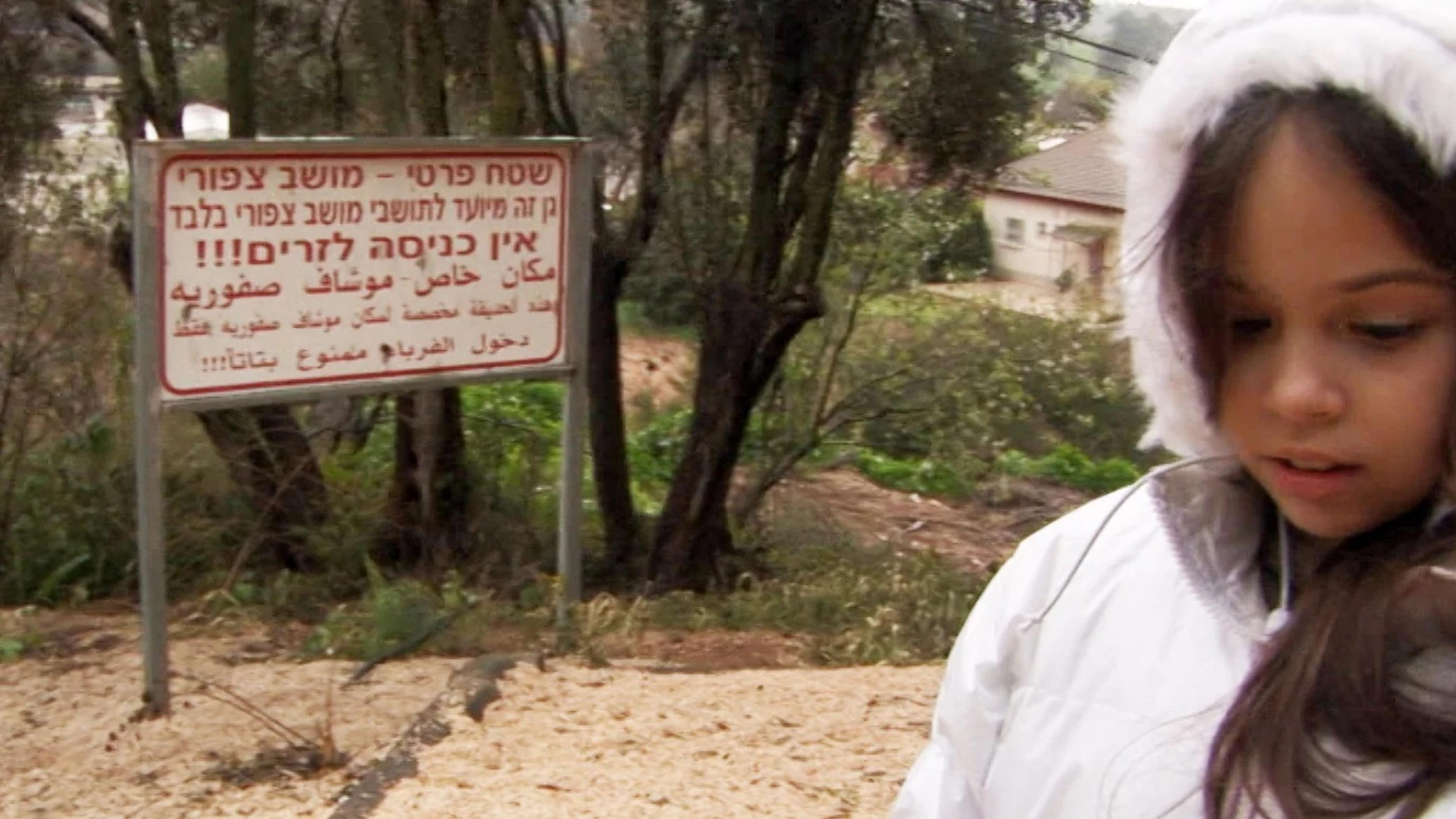 """Filmszene aus """"Once I entered the Garden"""": Ein Mädchen in einer Winterjacke blickt auf den Boden, neben ihm steht ein Hinweisschild in hebräischer und arabischer Schrift."""