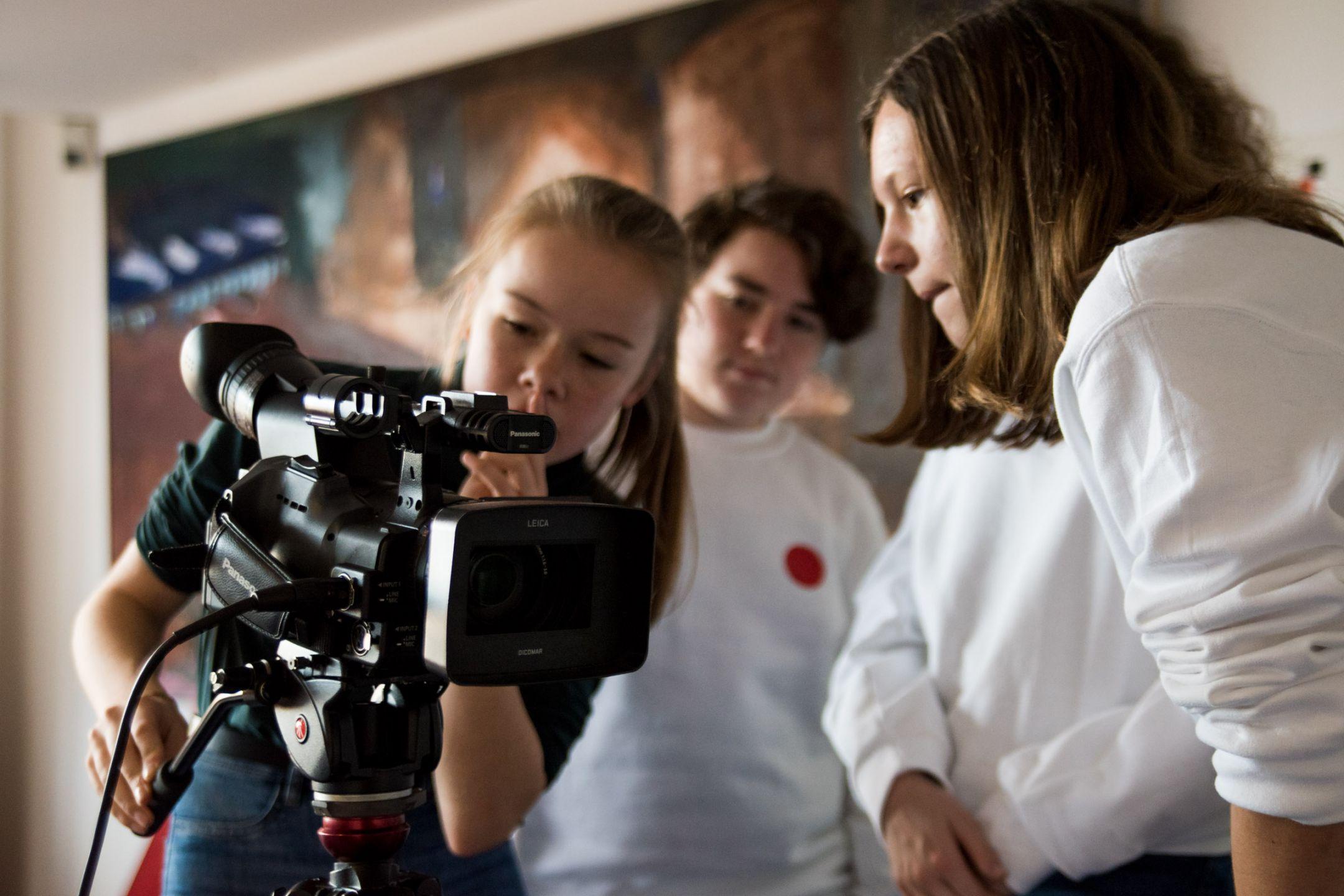 Drei Jugendliche in weißen DOK Pullis beugen sich über eine Kamera