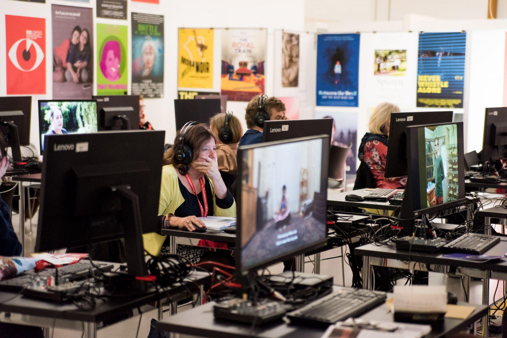 In einem Raum voller Poster sitzen Mensche an Computern, eine Frau guckt sehr konzentriert