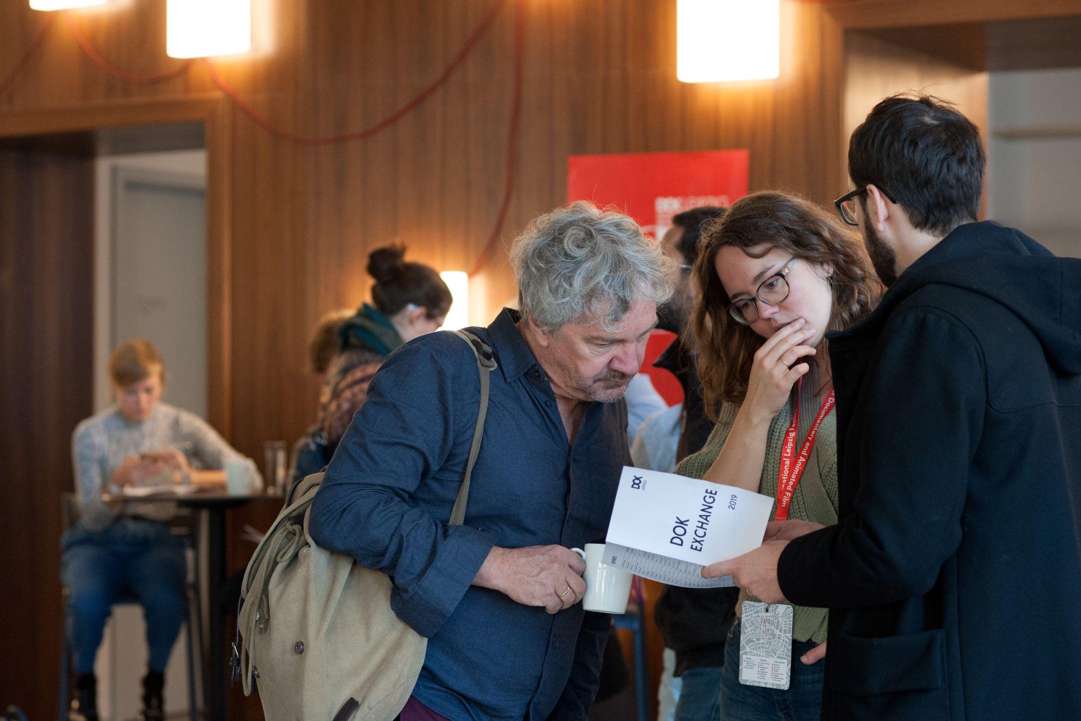 Zwei Männder und eine Frau schauen gemeinsam in ein Programmheft zu DOK Exchange