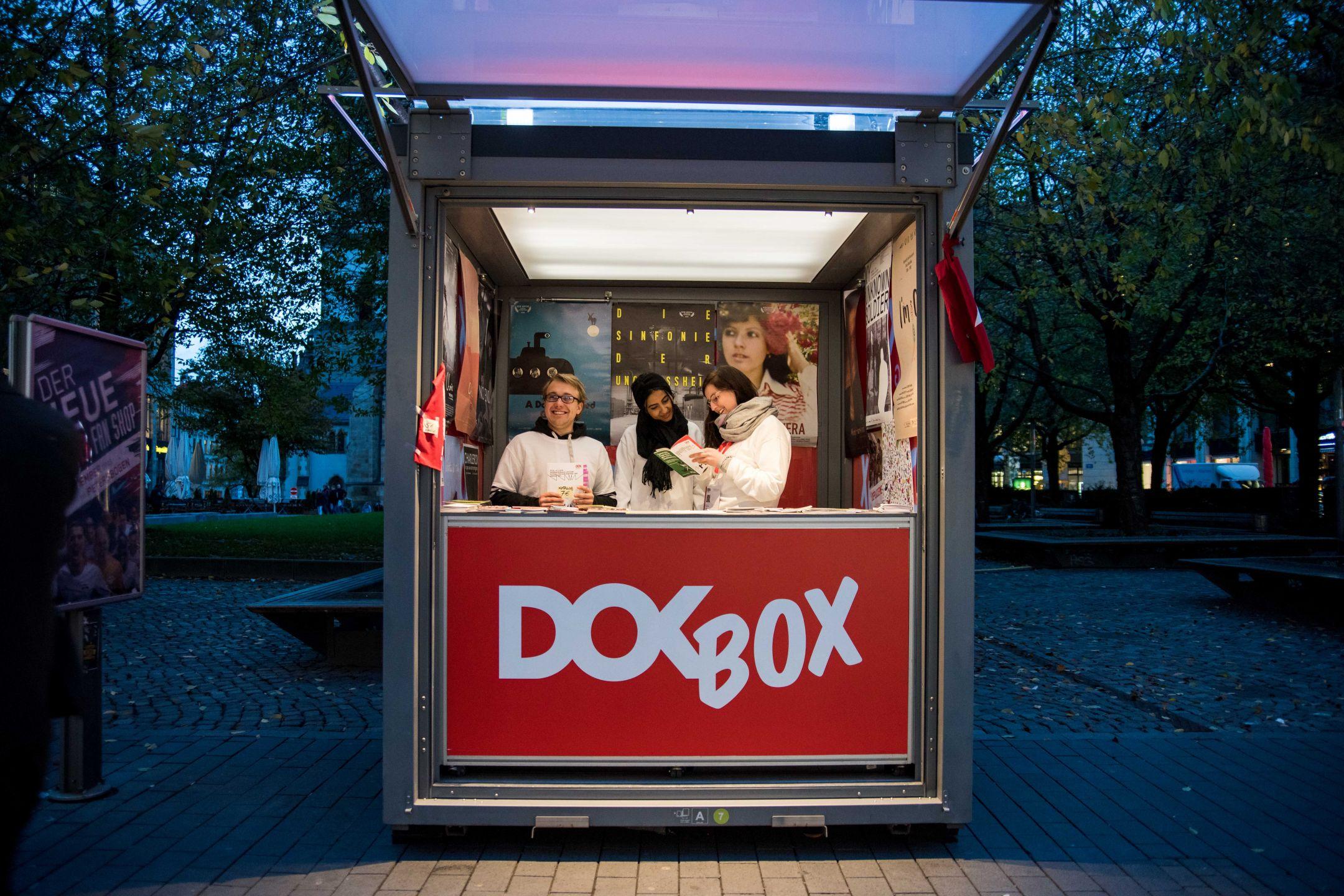 Drei Volunteers im blauen Abendlicht stehen in einer roten DOK Box und schauen in ein Programmheft.