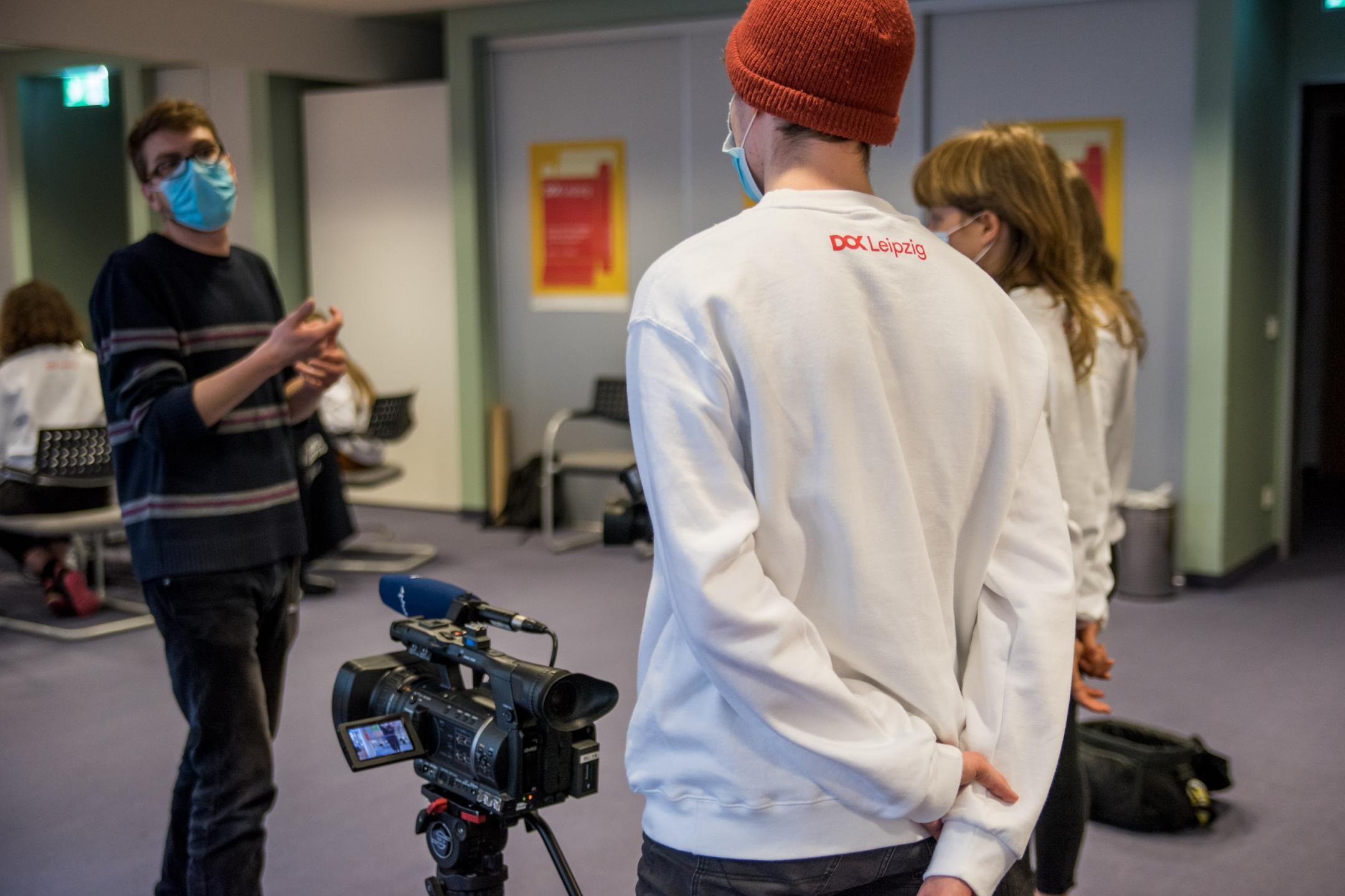 Zwei Jugendliche stehen hinter einer Videokamera und interviewen einen Mann.