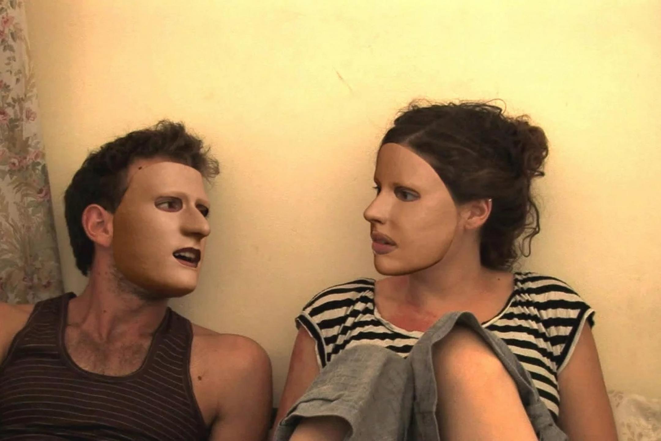 Filmszene aus Z32: Ein Mann und eine Frau sitzen nebeneinander an eine weiße Wand gelegt. Ihre Köpfe sind einander zugewandt. Beide tragen Masken, die ihr ganzes Gesicht überdecken.