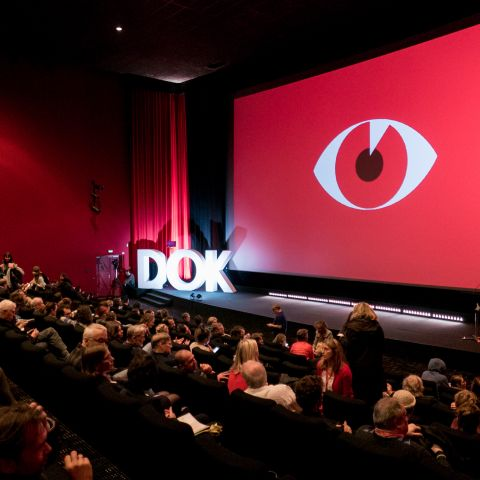 Red screen in a full cinema at the Opening of DOK Leipzig 2019. On the screen the festival motif.