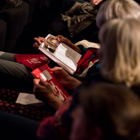 Female cinema visitors reading the DOK Leipzig programme brochure.