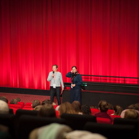Two people in front of the big red curtain on a stage in a full cinema.