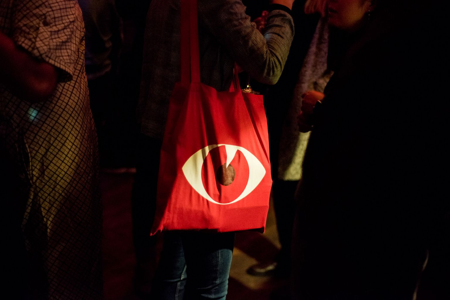 In a dark surrounding, one spotlight lights up the red dok bag with the festival motive, the eye
