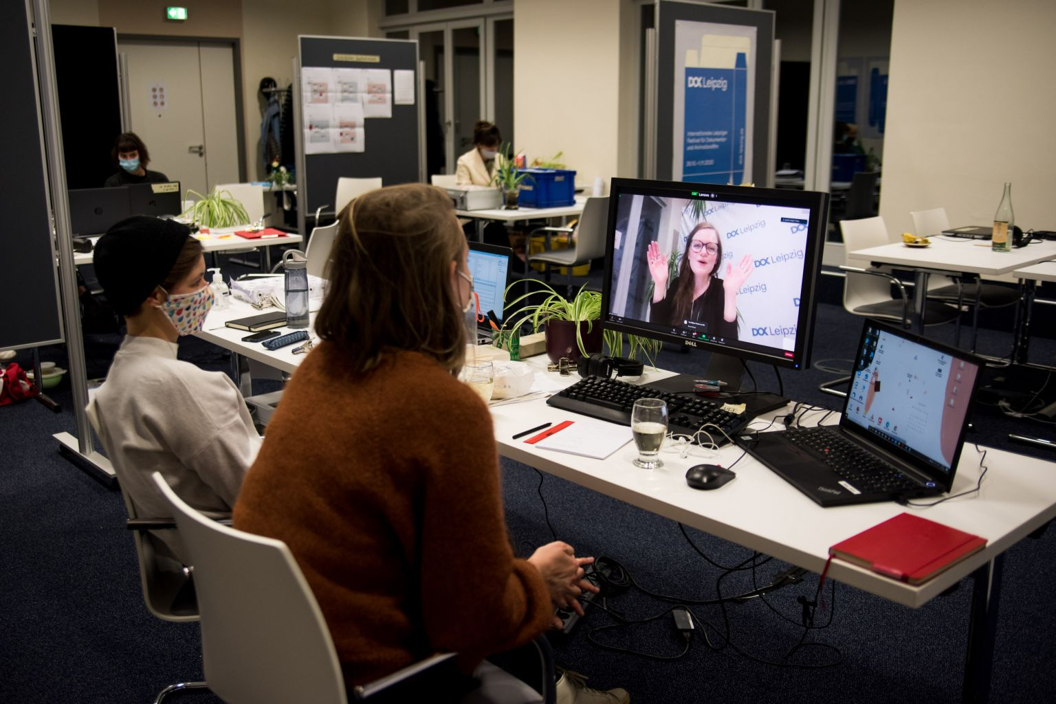 In an office two women with masks are sitting in front of a computer, on the screen a video of a cheering Brigid O'Shea can be seen