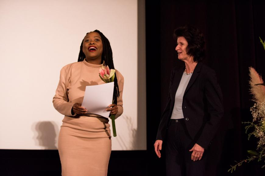 "Two women on a stage: the black woman on the left side is the director of the awarded film ""Black women and sex"" and is holding a certificate and flowers. The woman standing next to her is the state minister for art and culture."