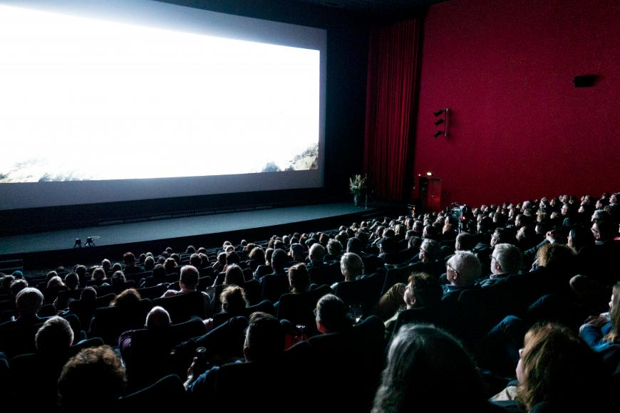 Cinema full of visitors who are looking to a white screen.