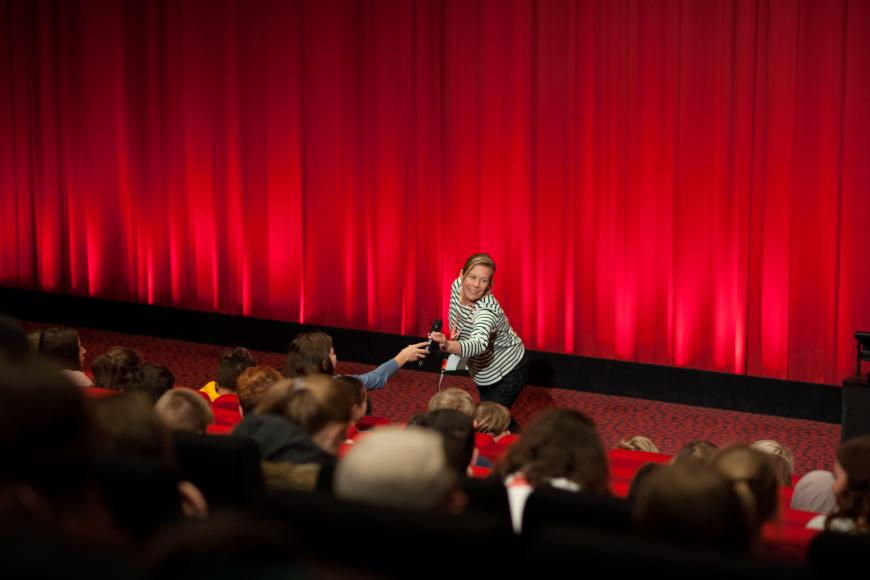 A moderator is standing in front of a red curtain on stage of a cinema hall. She bows forward and hands the microphone to a visitor in the first row
