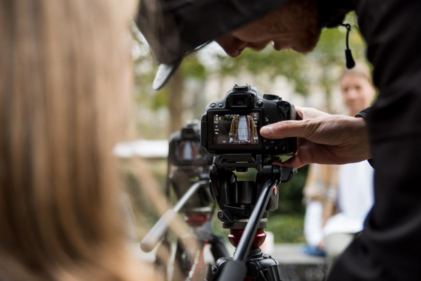 A teenager is bowed over a video camera, the spectator can see the viewfinder