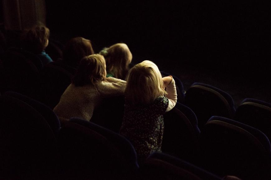 Four children in movie seats are looking excitedly at the screen.