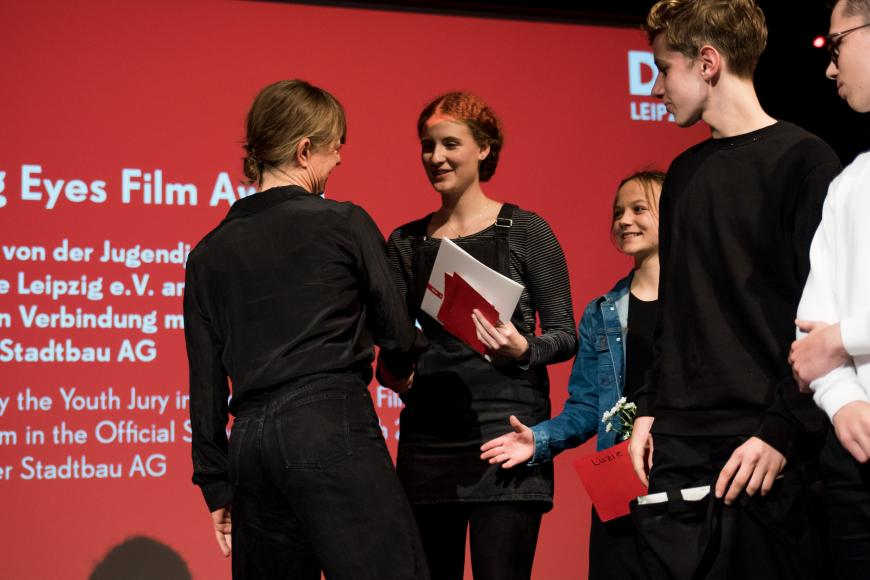 Four members of the youth jury congratulate a prize winner on stage