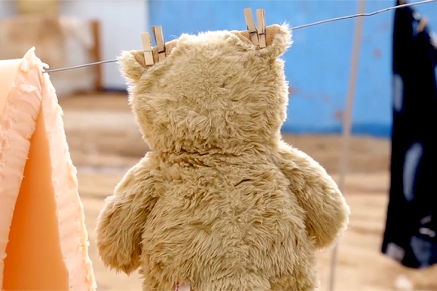 A teddy is hanging on a clothes line