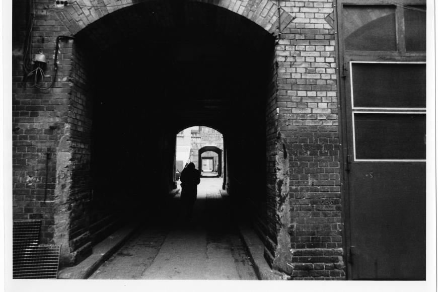 Black and White Filmstill: a house entrance in the shadow, the passage is built with bricks.