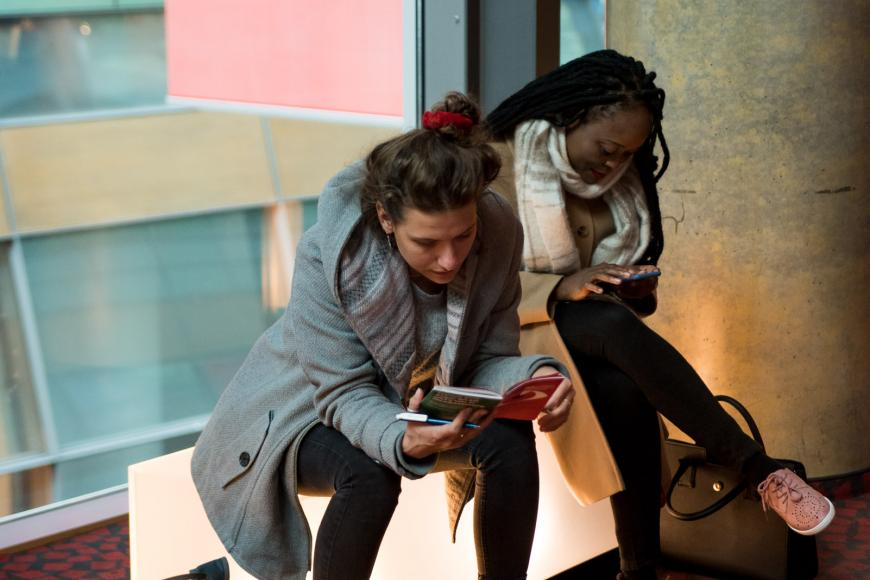 Two women are sitting on a bench, one of them is reading the printed programme and the other is scrolling on her smartphone