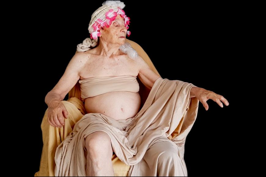 An old woman dressed in a flesh coloured cloth and a plastic flower crown is sitting on a chair in front of a black background