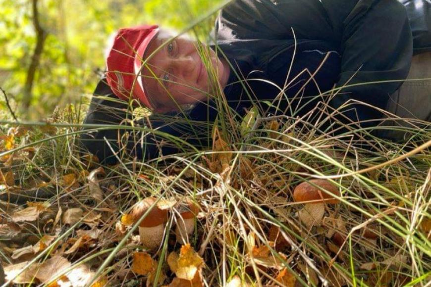 A man is lying on the forest floor smiling proudly at the camera, in front of him a couple mushrooms are growing in the grass