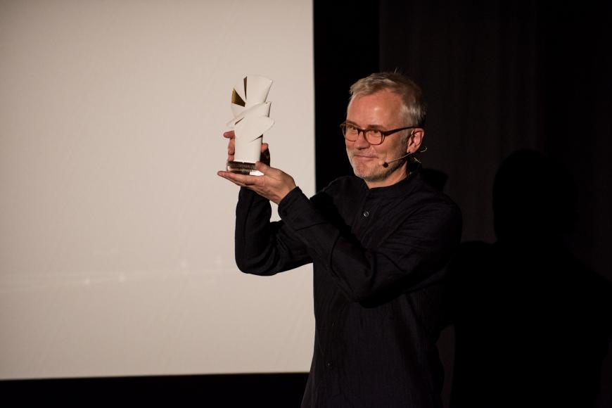 Festival director Christoph Terhechte presents a Golden Dove statue.