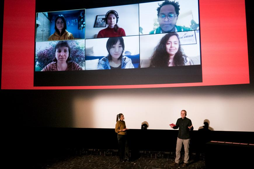 A woman and a man moderating in front of a cinema screen, where you can see the faces of six persons.